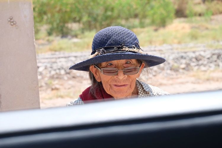 Elderly local woman with hat Female Charakter Blue Hat Car Window Local Woman Looking At Camera Senior Adult Sunglasses