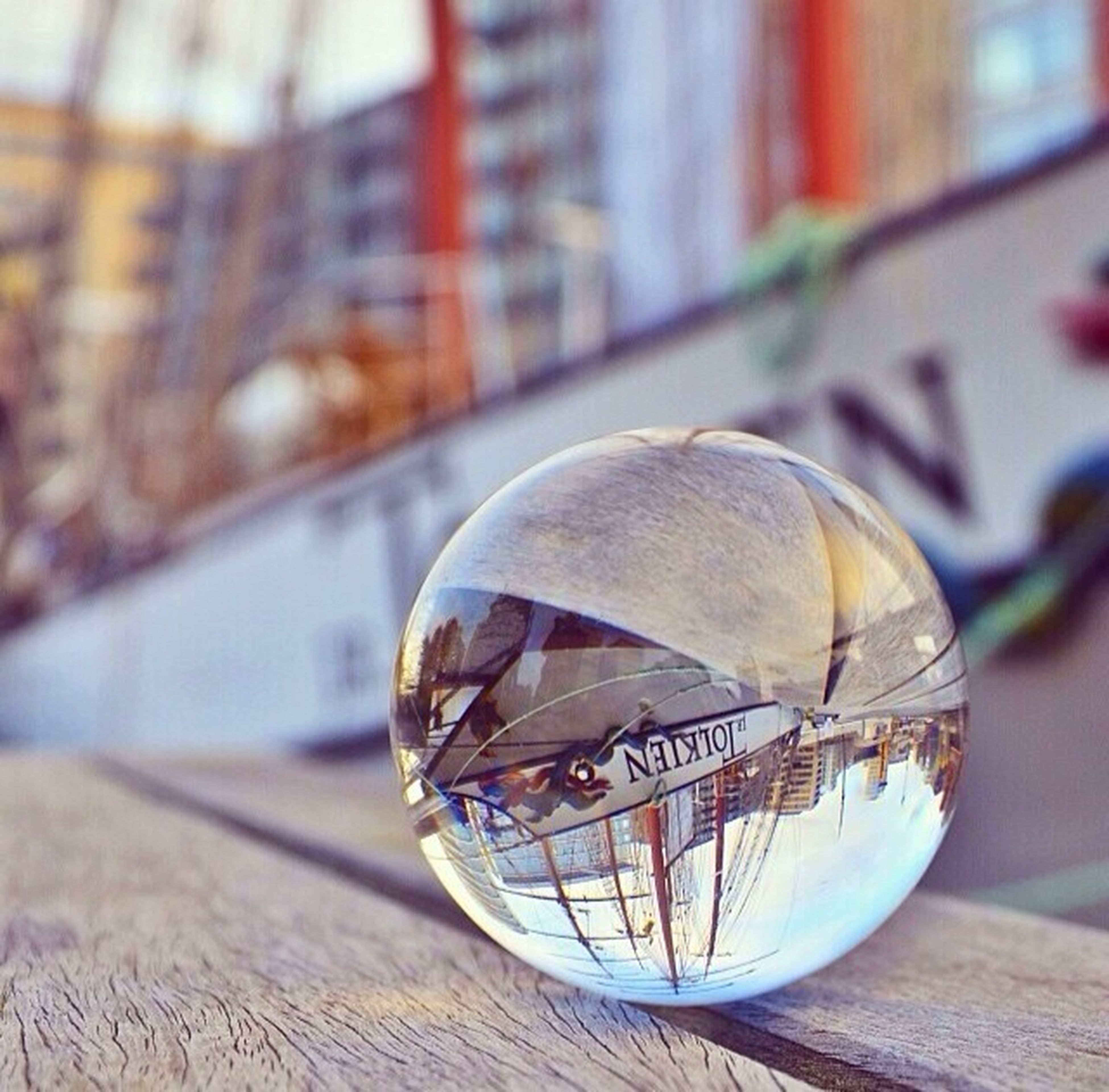 focus on foreground, table, close-up, still life, indoors, glass - material, selective focus, transparent, no people, day, text, single object, reflection, sphere, western script, communication, decoration, wood - material, wooden