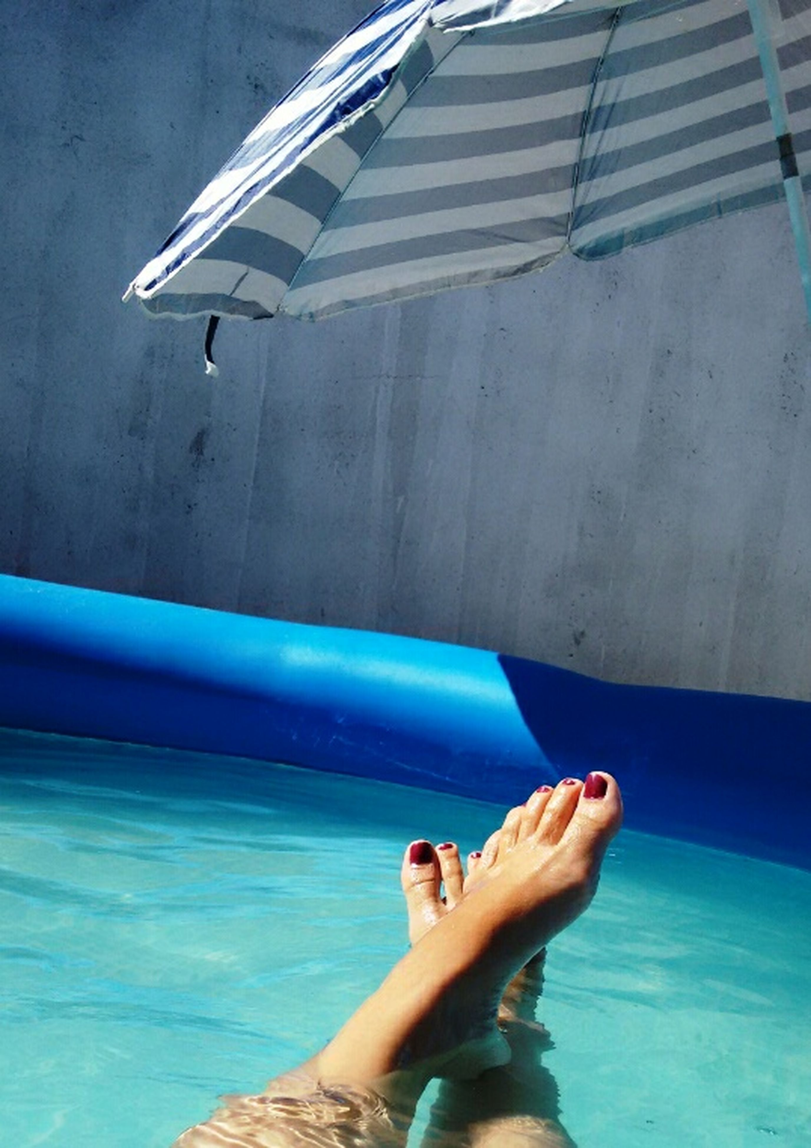 low section, person, swimming pool, lifestyles, part of, barefoot, personal perspective, leisure activity, blue, water, cropped, sea, human foot, men, holding