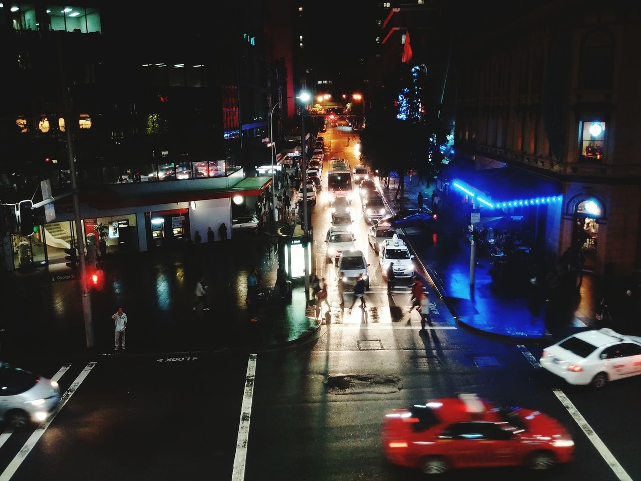illuminated, night, transportation, mode of transport, city, land vehicle, car, building exterior, architecture, street, built structure, street light, city street, road, lighting equipment, traffic, city life, on the move, the way forward, high angle view