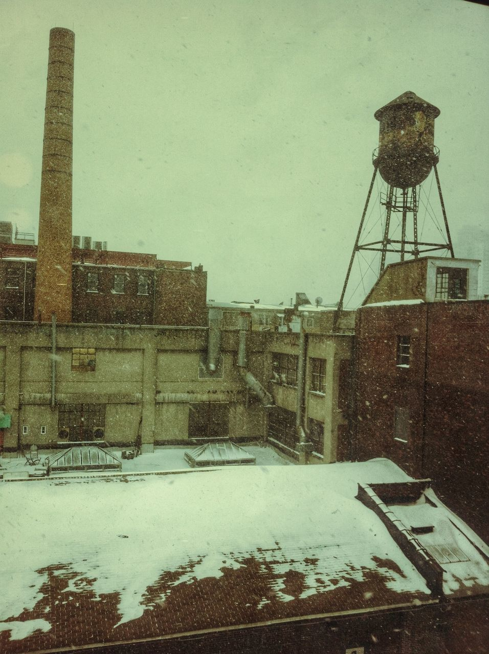 Industries and water tower during snowstorm