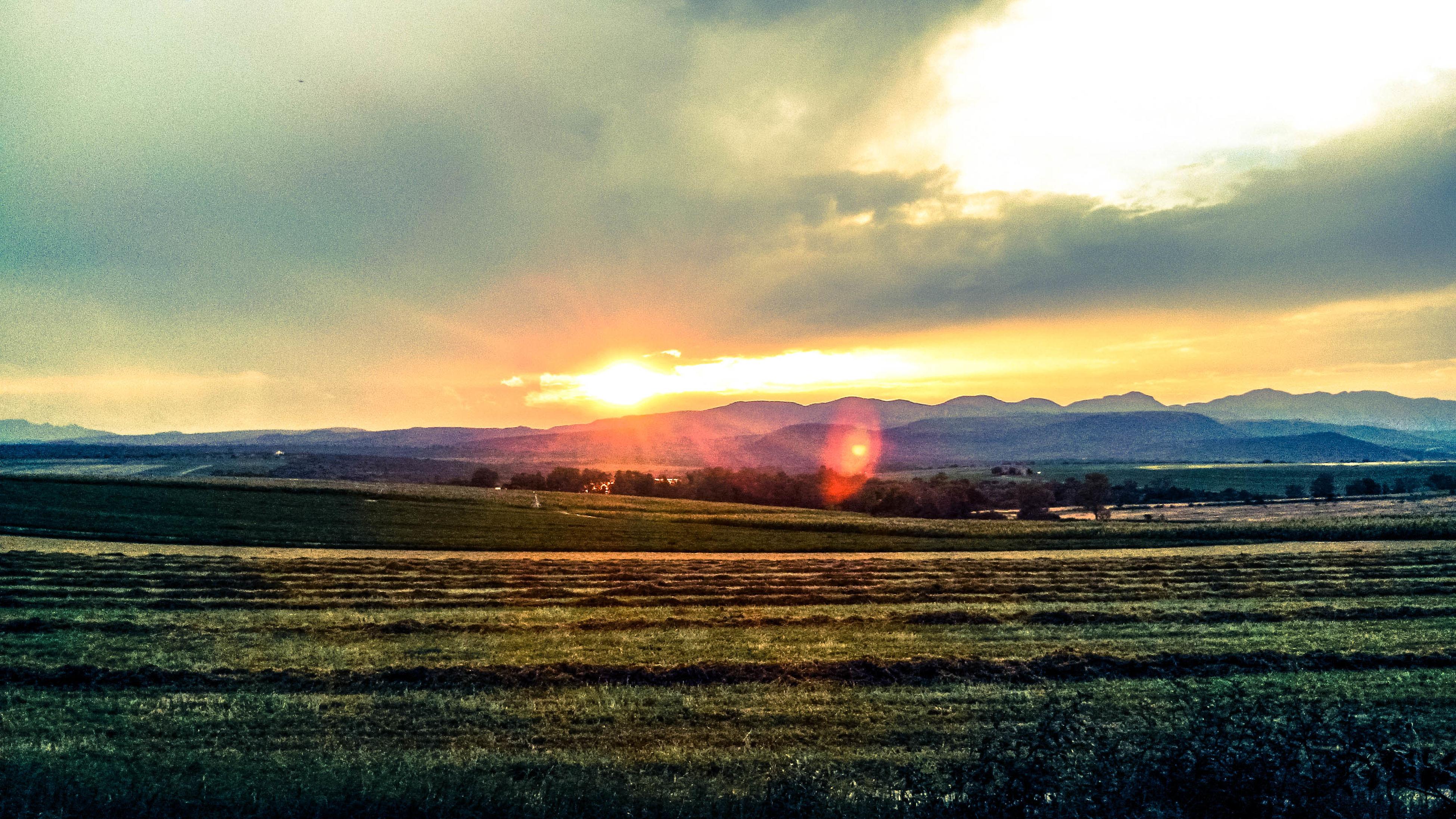 sunset, sun, tranquil scene, landscape, scenics, sky, tranquility, beauty in nature, field, rural scene, cloud - sky, nature, sunbeam, idyllic, orange color, sunlight, agriculture, grass, farm, lens flare