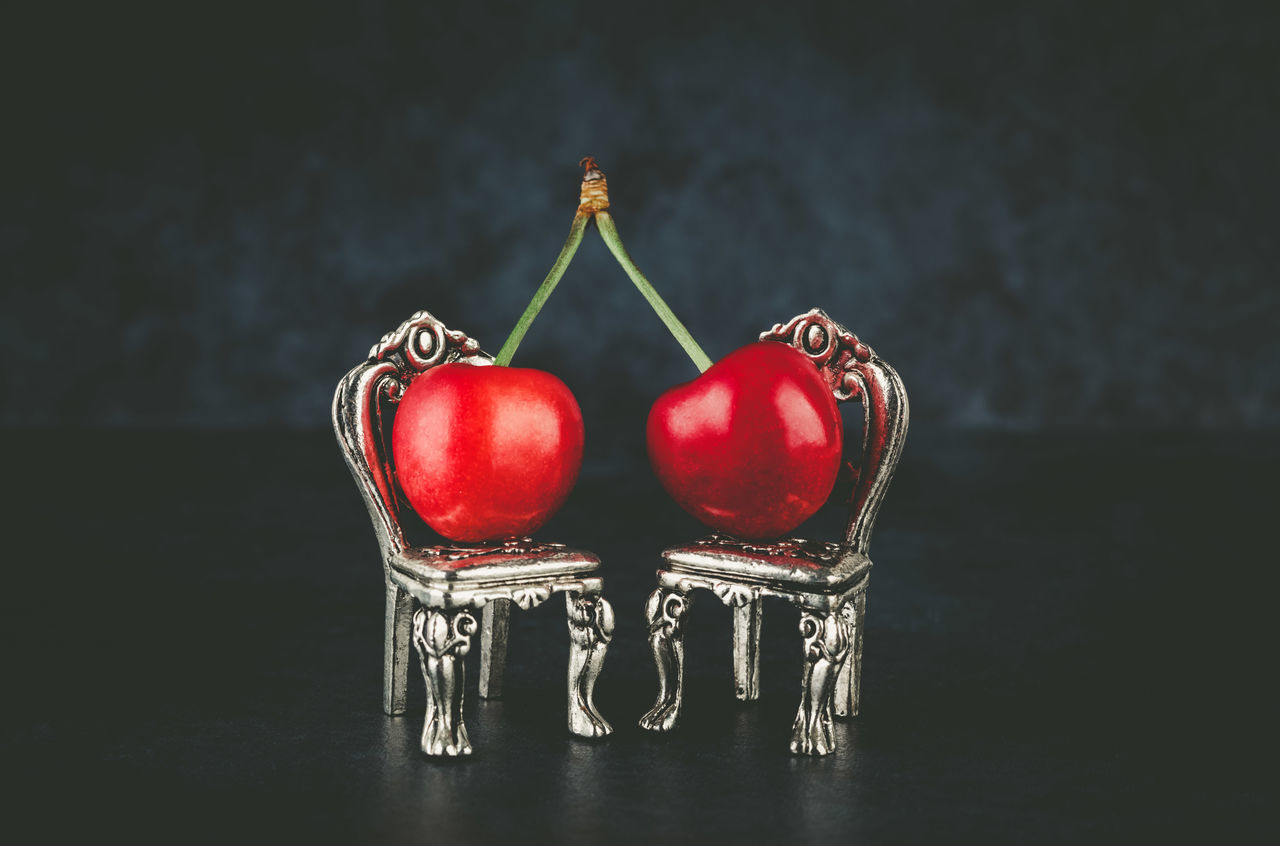 Couple of red cherries placed on beautiful silver vintage chairs on dark background with copy space. Relationship concept. Black Background Cherry Close-up Concept Copy Space Couple Day Food Freshness Fruit Healthy Eating Indoors  No People Ready-to-eat Red Relationship Sliver Chair Studio Shot Two Cherries