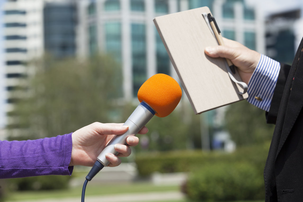 Journalist making press interview with microphone Adult Audio Businessman City Close-up Communication Day Holding Human Body Part Human Hand Interview Live Media Only Women Outdoors People Politician Pretty Radio Two People Women