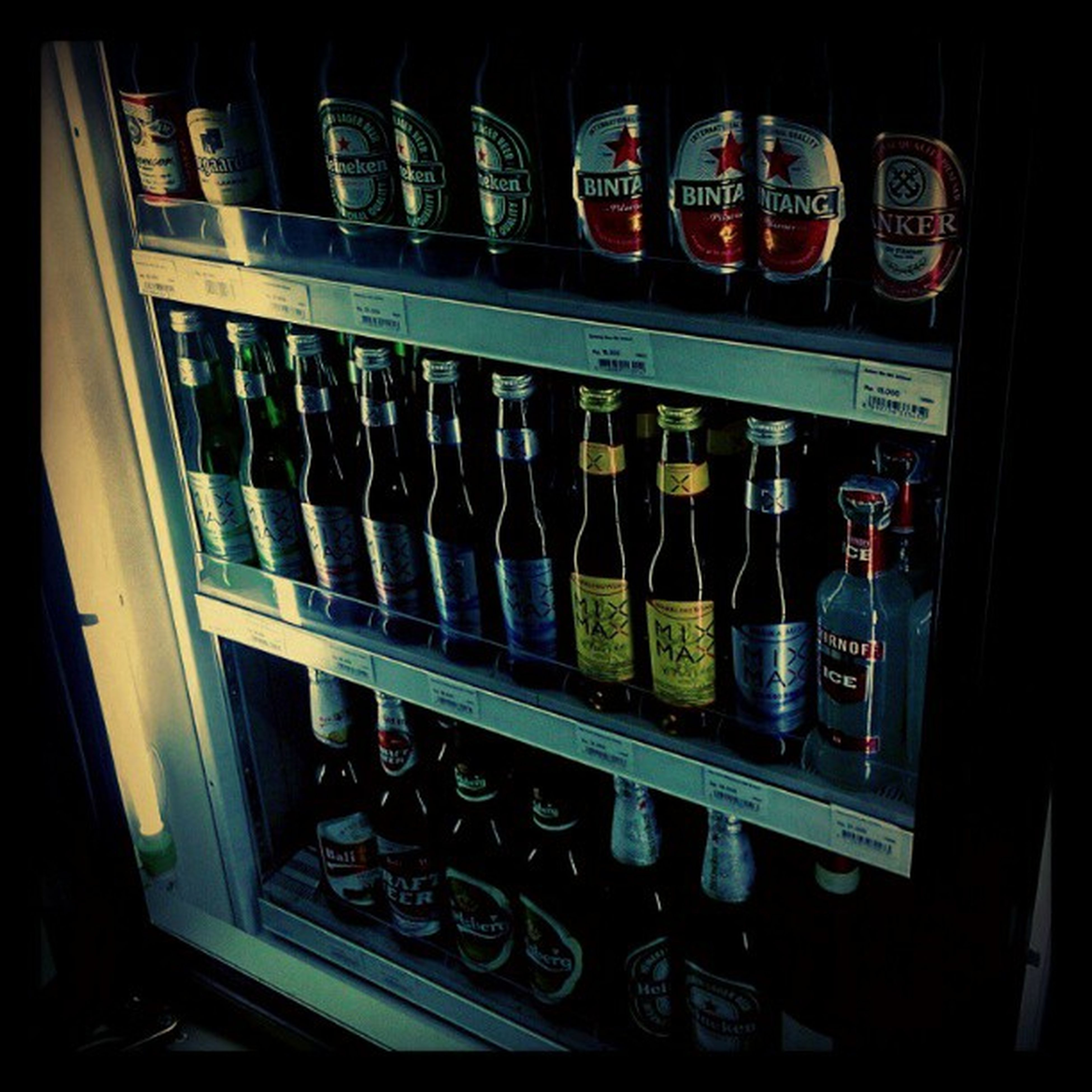 indoors, in a row, arrangement, shelf, order, large group of objects, abundance, choice, variation, text, window, repetition, store, no people, low angle view, glass - material, side by side, retail, hanging, still life