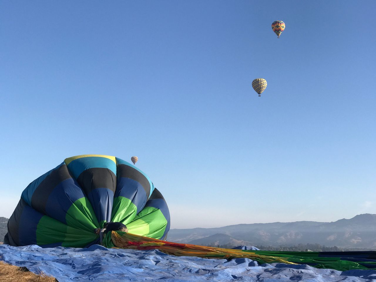 Clear Sky Mountain Transportation Hot Air Balloon Blue Tranquility Nature Flying Down Crash Fall Fail Deflated Air Scenics Mid-air Beauty In Nature Outdoors Geology Mountain Peak Mountain Range Physical Geography Green Color Extreme Terrain