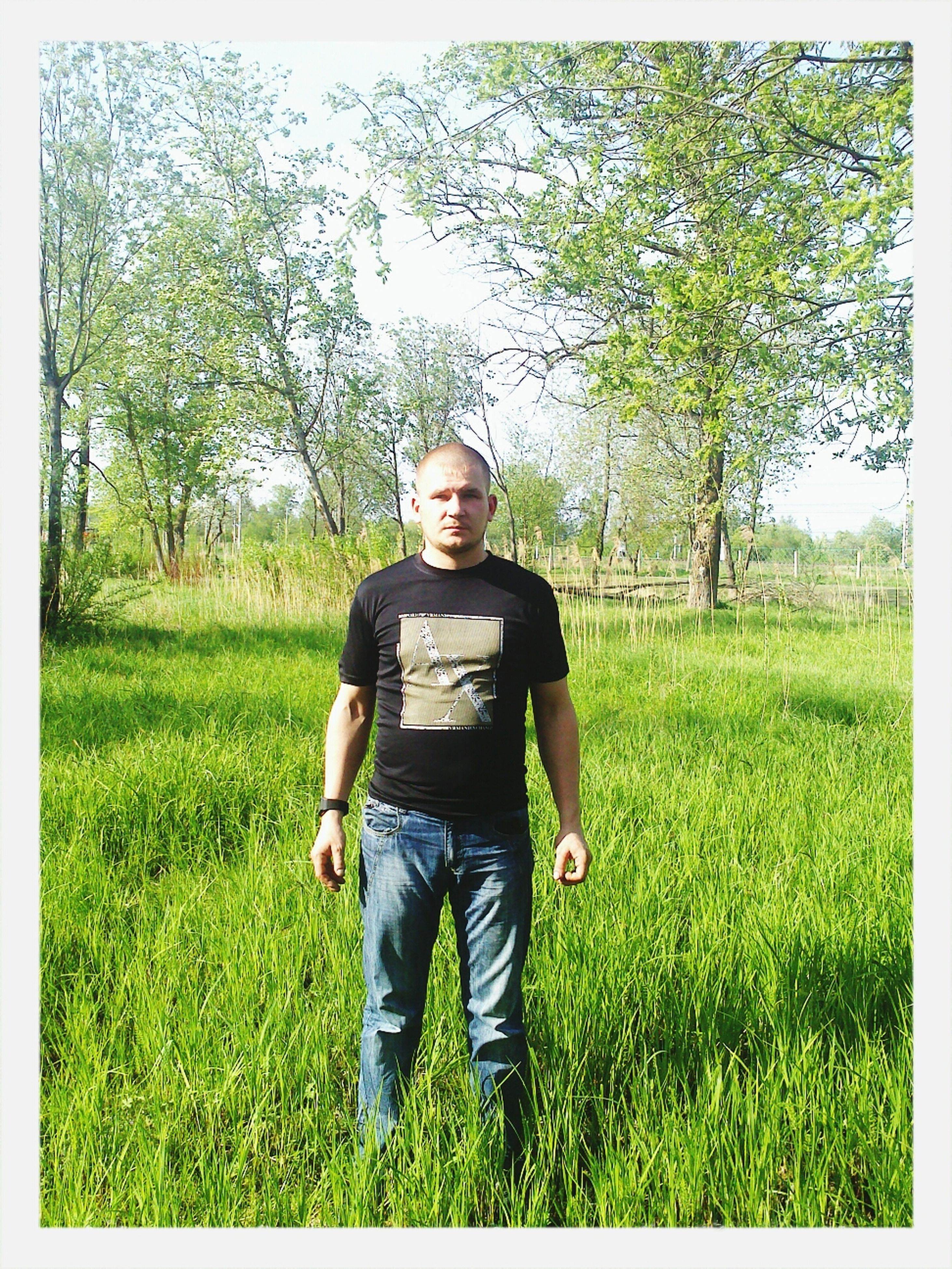 grass, transfer print, field, lifestyles, grassy, auto post production filter, leisure activity, green color, casual clothing, standing, growth, full length, plant, nature, landscape, person, men, tree
