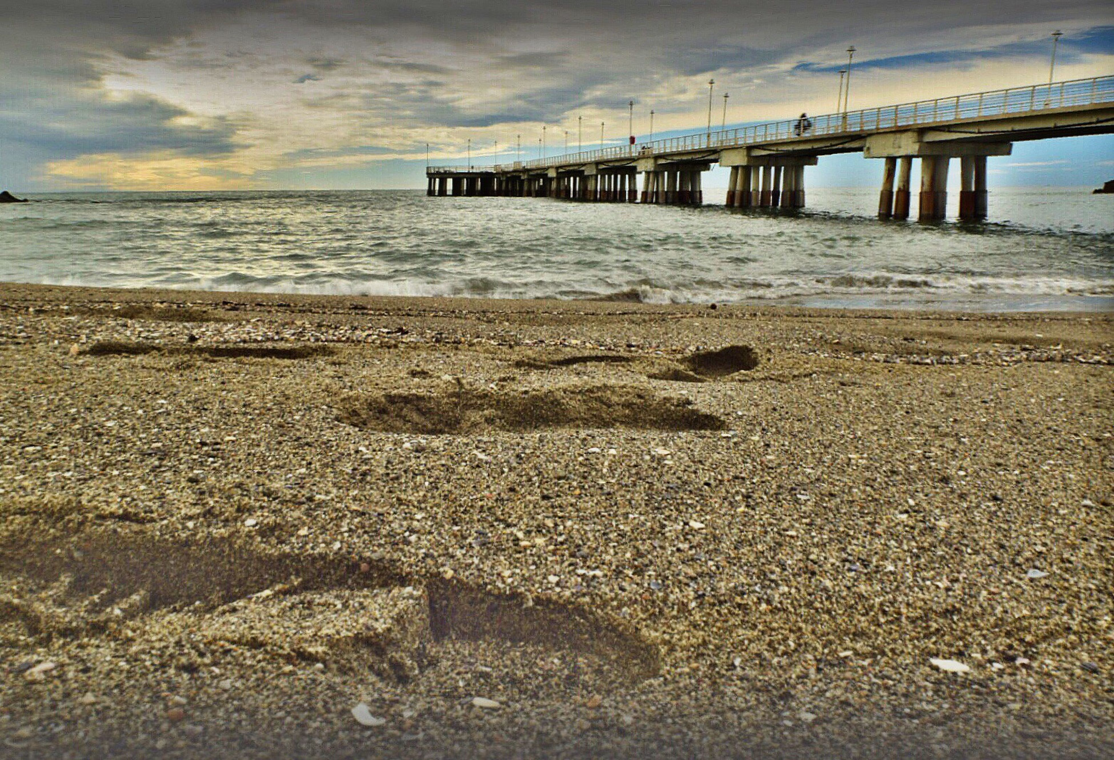sea, water, beach, sky, sand, shore, horizon over water, cloud - sky, built structure, tranquility, tranquil scene, scenics, pier, wave, architecture, cloud, nature, cloudy, beauty in nature, coastline