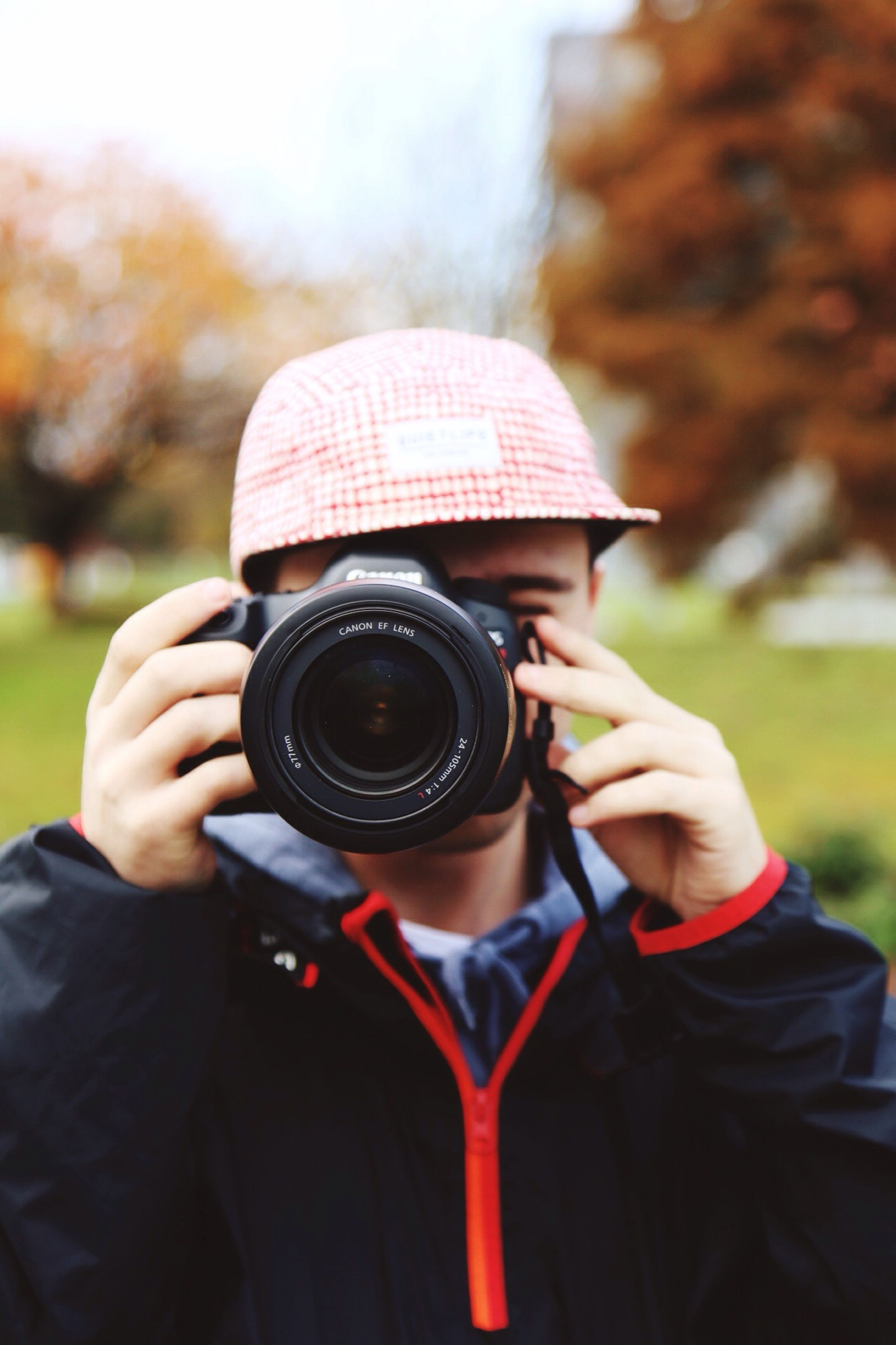 photography themes, camera - photographic equipment, holding, photographing, one person, focus on foreground, outdoors, technology, lifestyles, photographer, real people, slr camera, close-up, day, digital single-lens reflex camera, flat cap, sky, human hand, people, adult