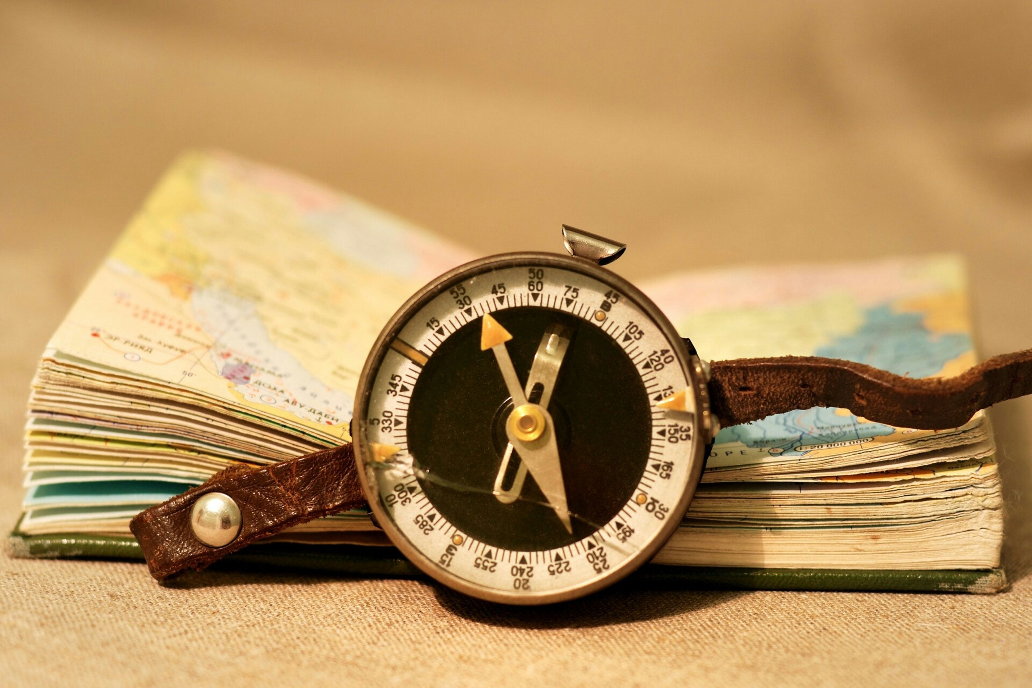 text, communication, indoors, retro styled, close-up, number, old-fashioned, time, still life, antique, clock, old, single object, western script, metal, focus on foreground, table, wood - material, man made object, technology