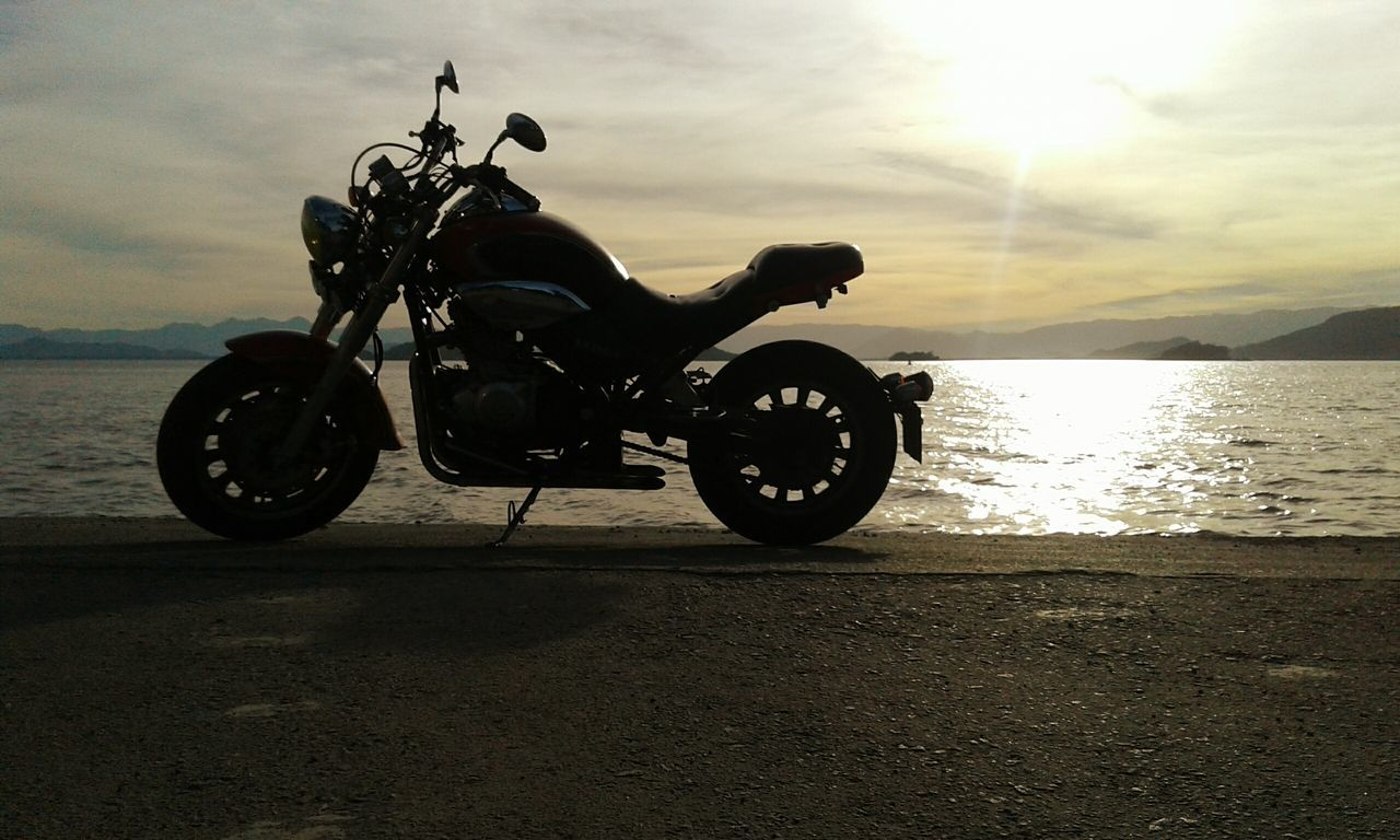 motorcycle, transportation, mode of transport, sunset, land vehicle, sky, sea, outdoors, silhouette, water, sunlight, stationary, nature, scooter, horizon over water, no people, day