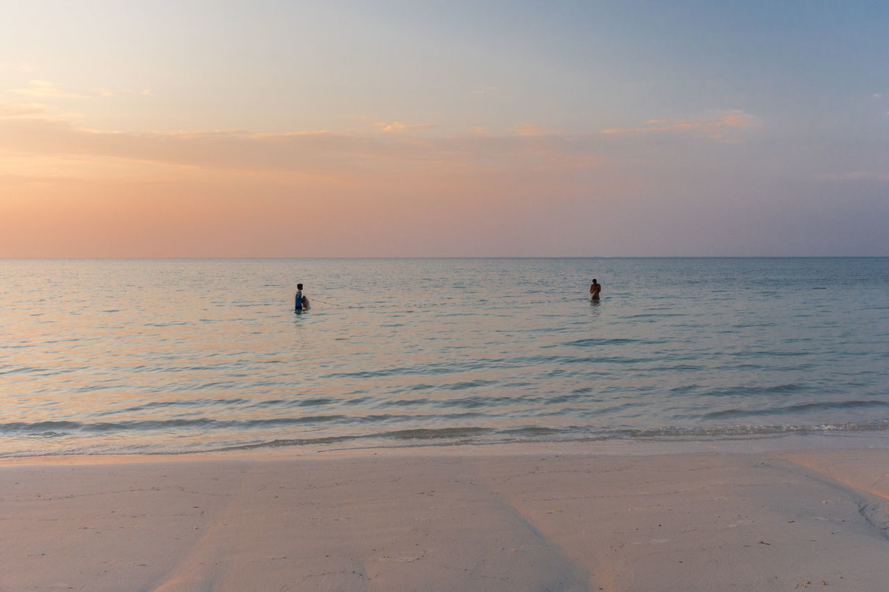 2 fishermen catch fish with a net off the beach at sunset. Beach Blue Calm Catch Clouds Clouds And Sky Day Fisherman Fishing Nature Ocean Orange Outdoors People Sea Still Sunset Tranquil Scene Tranquility Vacations Water White Sand