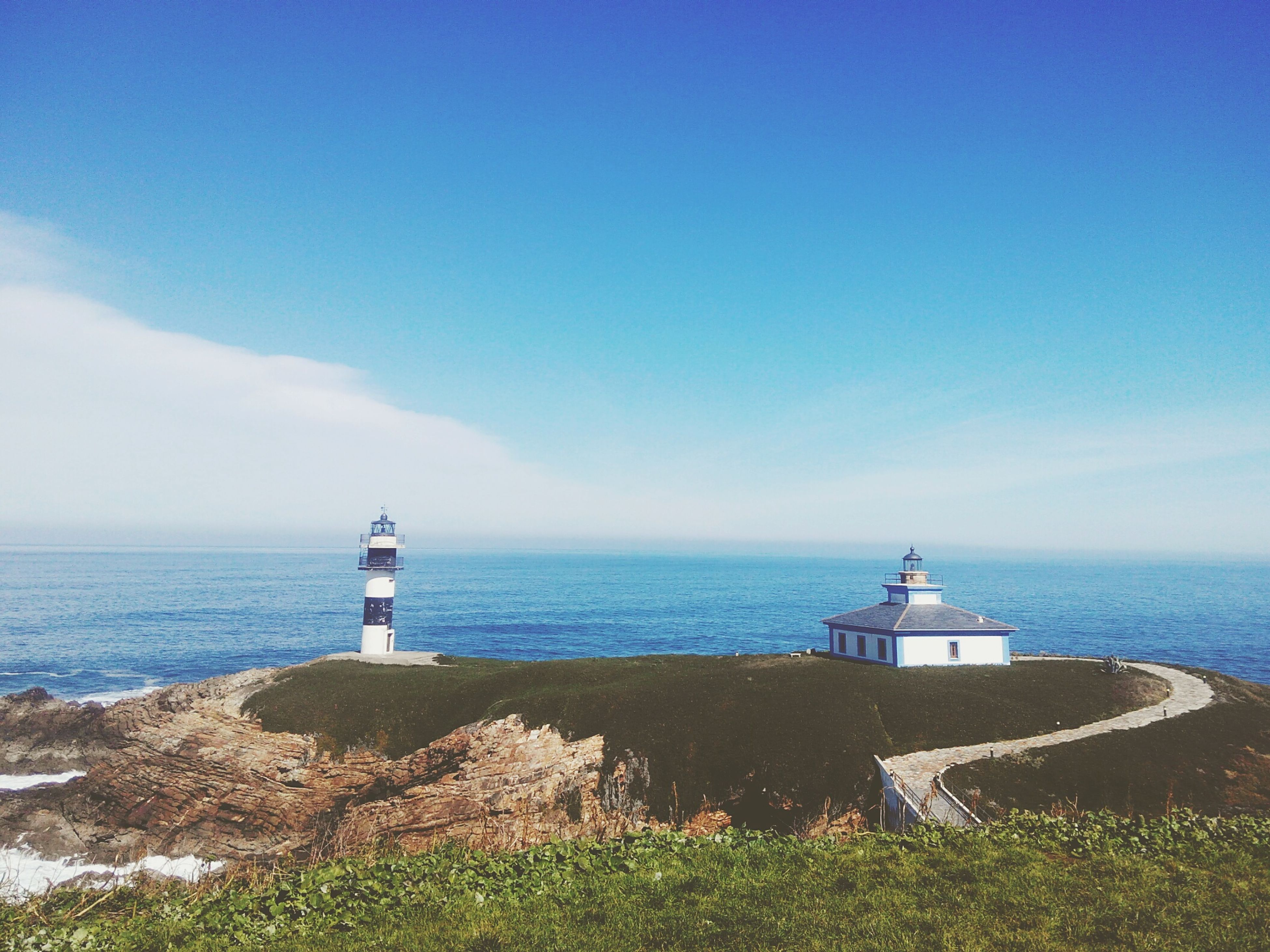 lighthouse, sea, guidance, horizon over water, direction, protection, water, safety, security, built structure, architecture, sky, tower, tranquility, tranquil scene, blue, building exterior, scenics, beauty in nature, nature