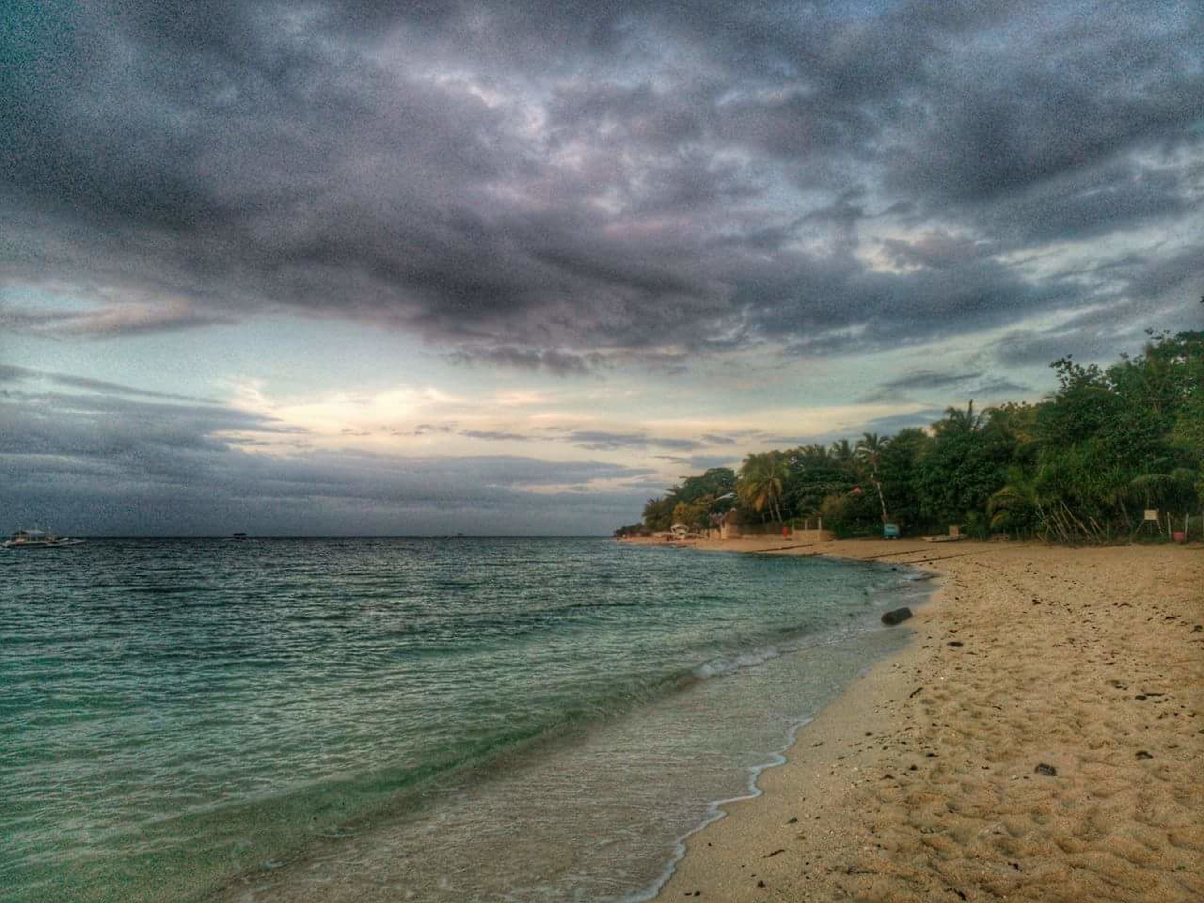 sea, cloud - sky, beach, tree, sky, beauty in nature, nature, scenics, outdoors, horizon over water, tranquil scene, sand, dramatic sky, tranquility, no people, water, landscape, storm cloud, day