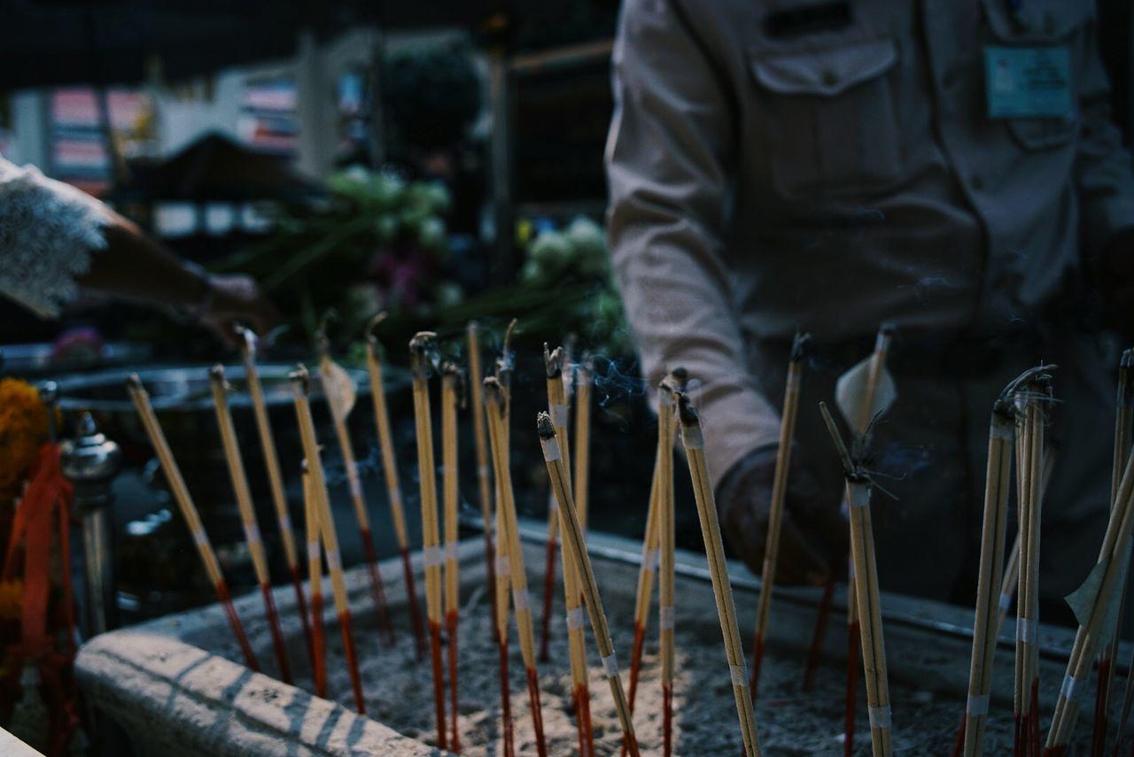 Midsection Of Man Burning Incense At Grand Palace