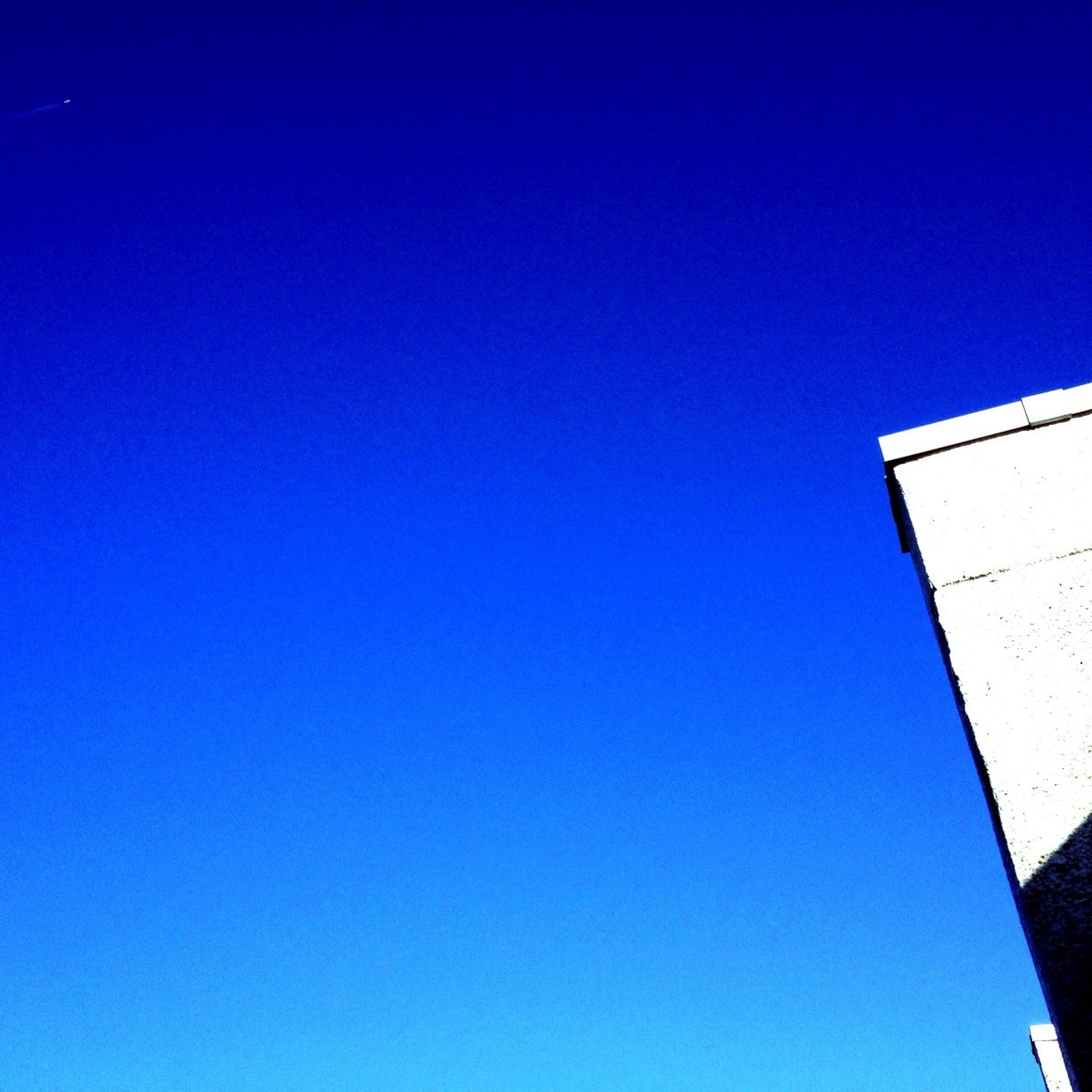 blue, clear sky, architecture, low angle view, copy space, built structure, building exterior, building, high section, day, outdoors, no people, sunlight, wall - building feature, residential structure, part of, house, wall, residential building, nature