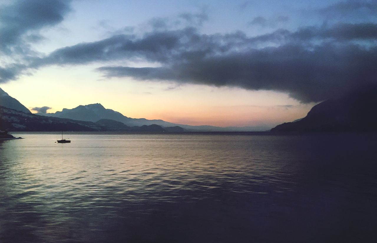 mountain, scenics, beauty in nature, water, nature, tranquil scene, tranquility, sky, sunset, sea, cloud - sky, idyllic, dramatic sky, outdoors, mountain range, no people, silhouette, waterfront, travel destinations, nautical vessel, day