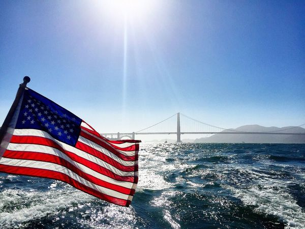 Connection Patriotism American Flag Flag Suspension Bridge Identity Bridge - Man Made Structure Culture Golden Gate Bridge National Flag Water Clear Sky Travel Destinations Blue Tourism Famous Place Built Structure Engineering Sun Architecture Golden Gate Bridge Catamaran Bay Area