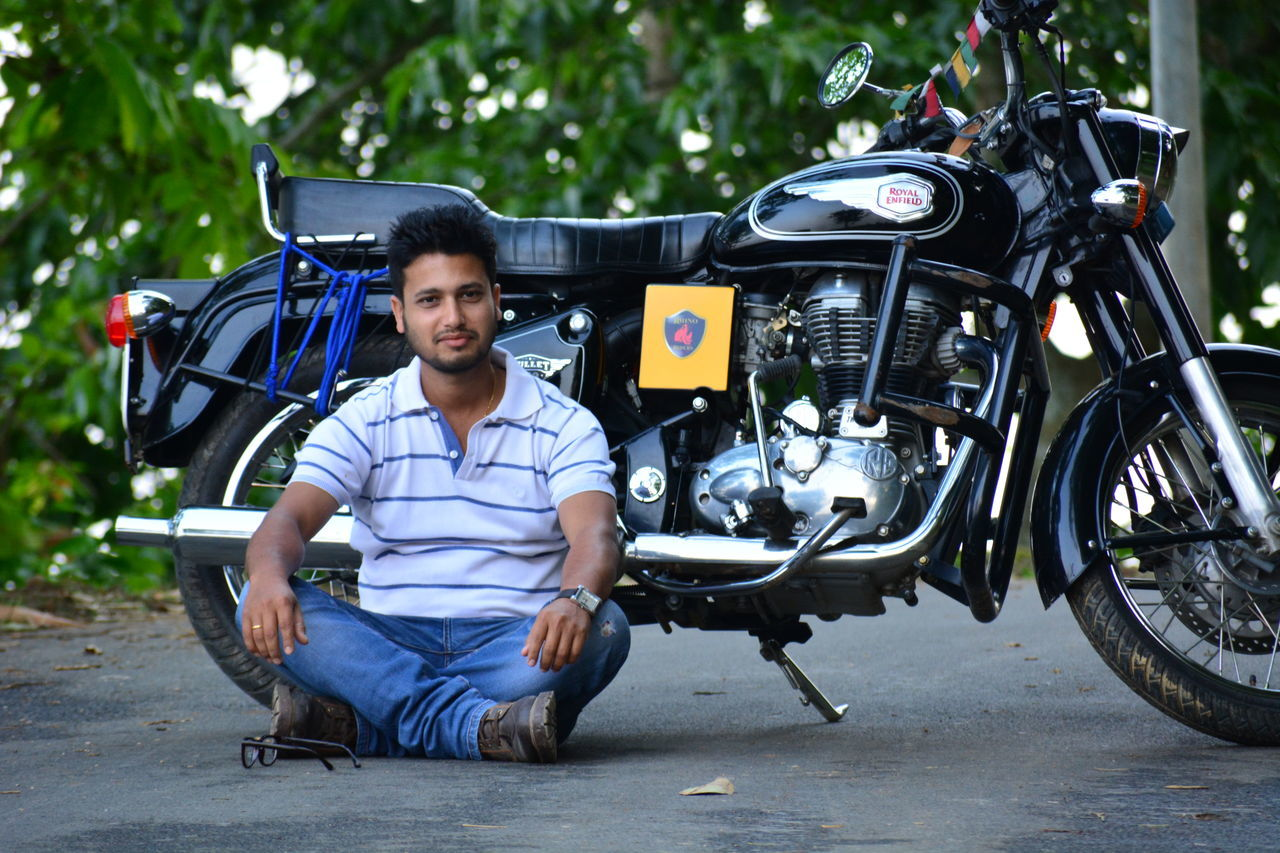 motorcycle, sitting, transportation, casual clothing, one person, young adult, front view, outdoors, real people, day, full length, confidence, portrait, looking at camera, one young man only, smiling, one man only, adults only, lifestyles, biker, tree, only men, adult, people