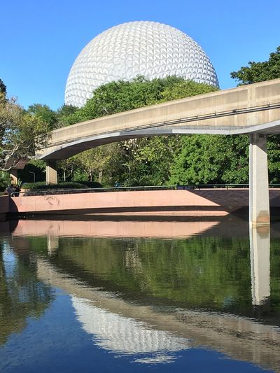 Epcot Epcot Disney World Disney Water Reflection Architecture Built Structure Day Travel Destinations Sunlight Dome Religion Spirituality Waterfront Place Of Worship Building Exterior Tree Outdoors No People Blue Sky Shadow Clear Sky
