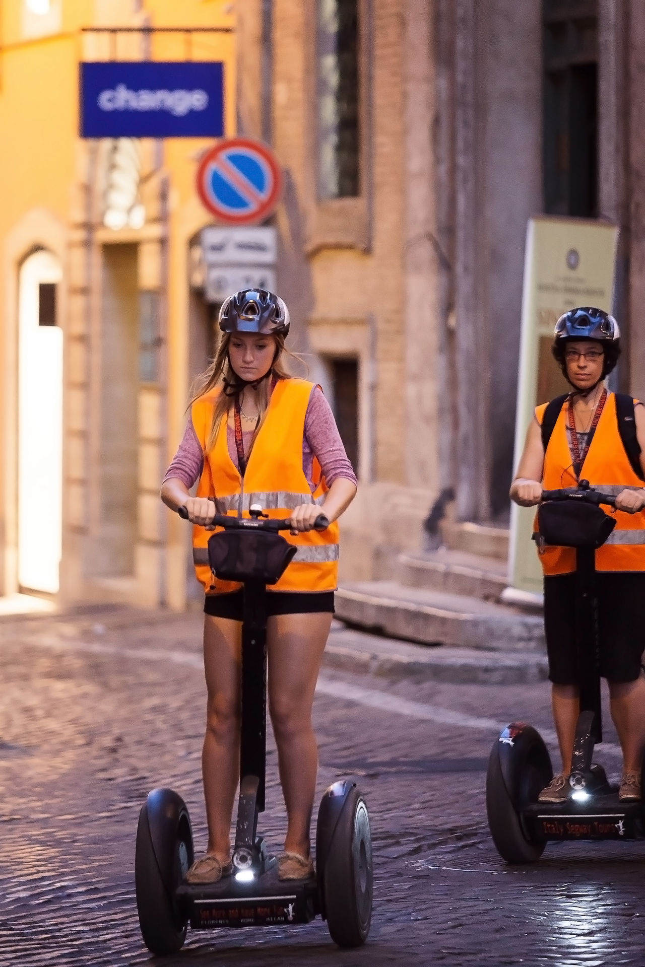 Rome, Italy - August 3, 2016: Two girls pass through the narrow streets of the city center with the help of a modern segway. Alley City City Life Cobblestones Day Girls Helmet Lifestyles Means Of Transport Modern Move New Technology Object Outdoors Reflective Vest Rome Segways Street