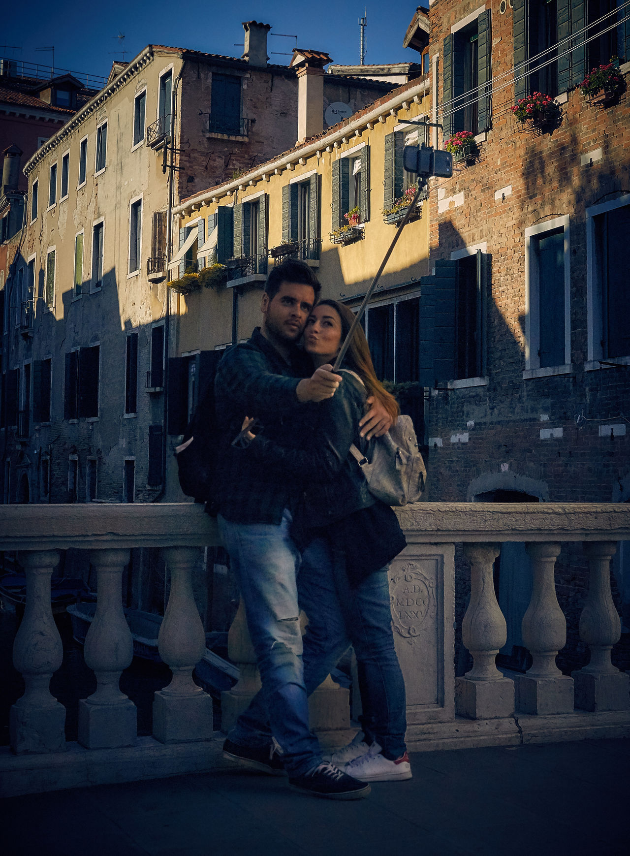 Modern Love Architecture Building Built Structure Casual Clothing City City Life Couple Day Front View Happiness Honeymoon Hug Leisure Activity Lifestyles Outdoors Person Portrait Selfie Stick Smiling Standing Tech Technology Technology Everywhere The Street Photographer - 2016 EyeEm Awards Toothy Smile