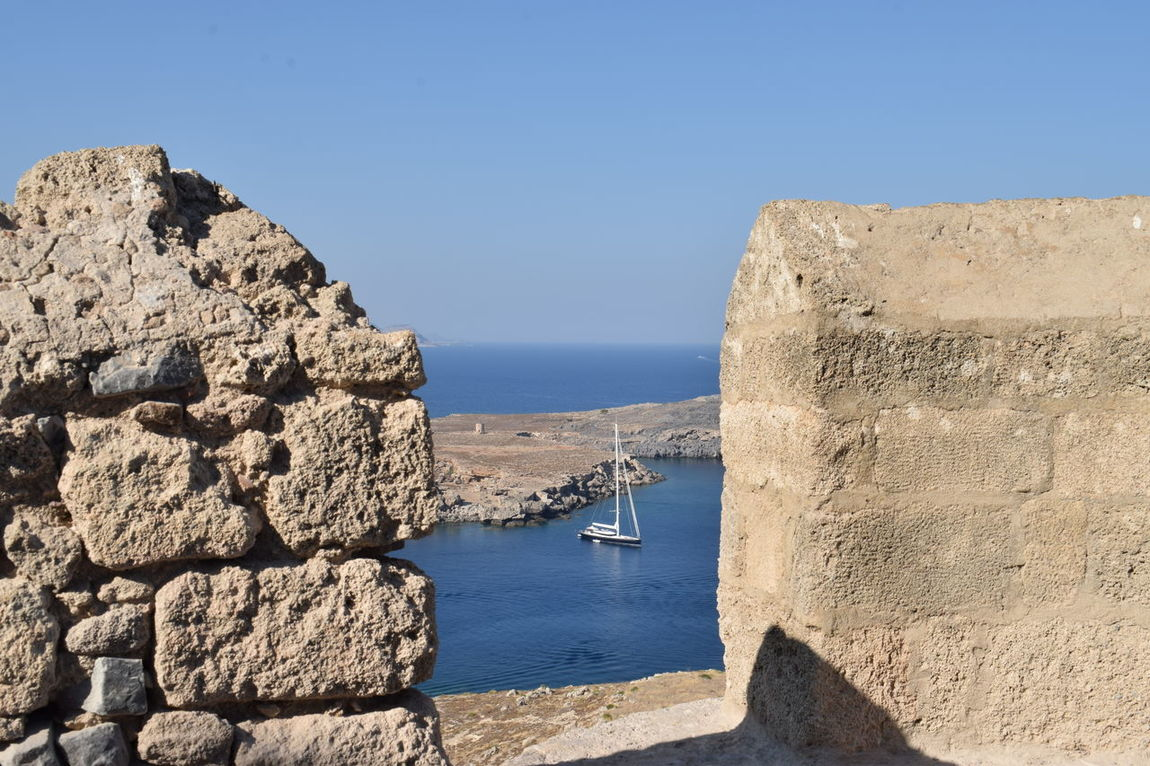 A view from the Lindos fortress, Rhodes, Greece Rhode Island View Blue Building Exterior Built Structure Clear Sky Day Lindos Lindos Greece Nature Nautical Vessel No People Outdoors Rock - Object Sailing Ship Sea Sky Sunlight Tranquility View From Above View From The Fortress Water