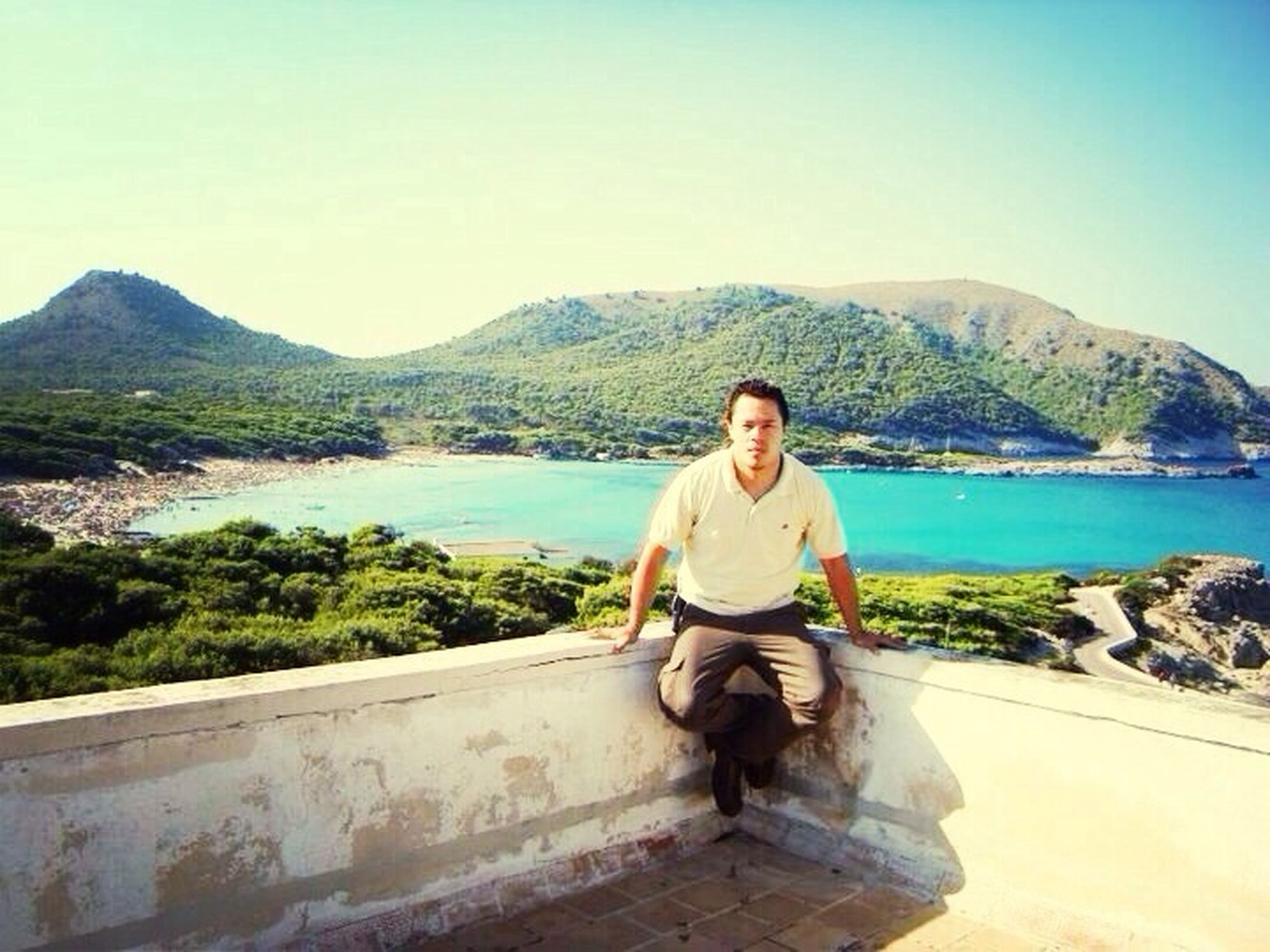 clear sky, mountain, water, copy space, young adult, lifestyles, casual clothing, leisure activity, person, mountain range, portrait, sea, young men, full length, looking at camera, sitting, beauty in nature, scenics