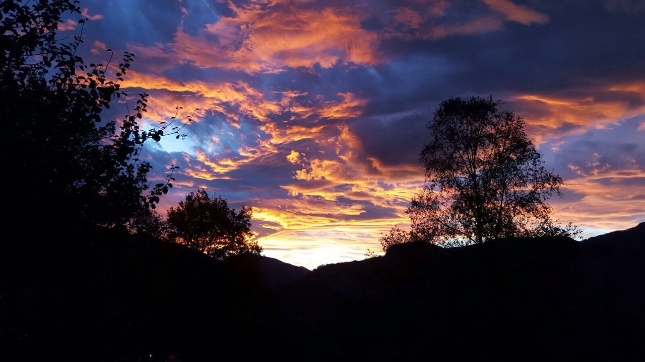 sunset, silhouette, tree, sky, nature, beauty in nature, scenics, cloud - sky, tranquil scene, dramatic sky, tranquility, no people, outdoors, mountain, low angle view, landscape, day