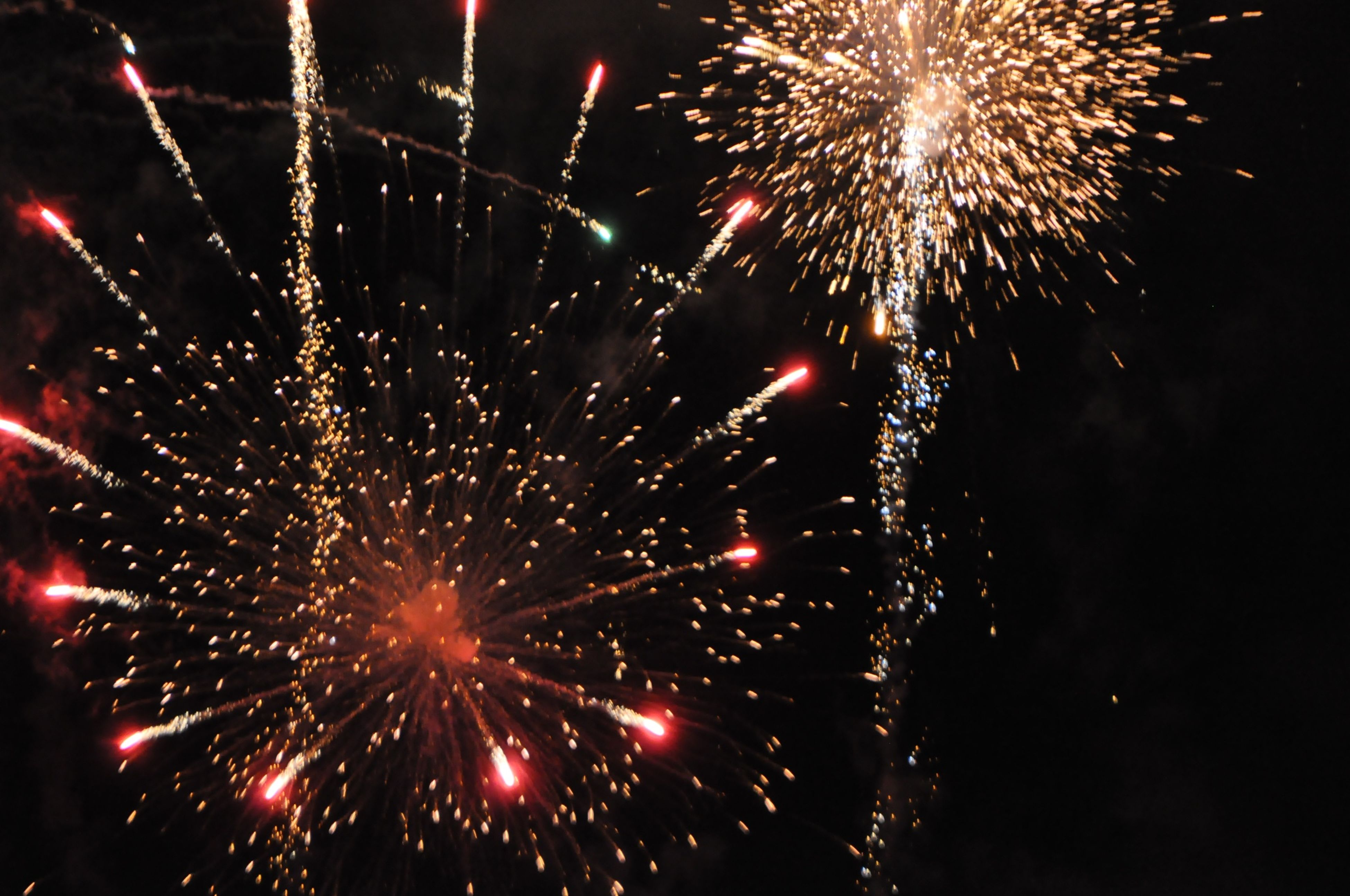 firework display, celebration, night, illuminated, exploding, firework - man made object, long exposure, event, glowing, motion, arts culture and entertainment, firework, sparks, entertainment, low angle view, celebration event, blurred motion, multi colored, sky, awe