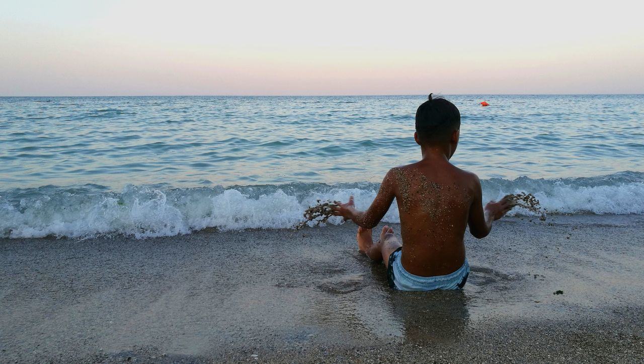 sea, water, real people, beach, horizon over water, rear view, shore, one person, beauty in nature, nature, sunset, lifestyles, scenics, shirtless, leisure activity, sand, wave, boys, clear sky, outdoors, standing, sky, childhood, men, full length, day, people
