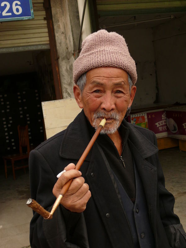 Alley Casual Clothing Chengdu China Confidence  Cool Hat Front View Happiness Hat Holding Lifestyles Looking At Camera Old Man Person Pipe Pipe Smoking Real People Smoking Smoking Old Man Smoking Pipe Standing Natural Light Portrait People And Places