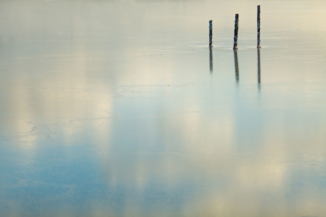 Three pilings protrude through a layer of new ice that is reflecting the sky. Beauty In Nature Clear Sky Cold Day Flawless Freezing Frozen Ice Nature New No People Outdoors Reflection Sky Water Waterfront Winter