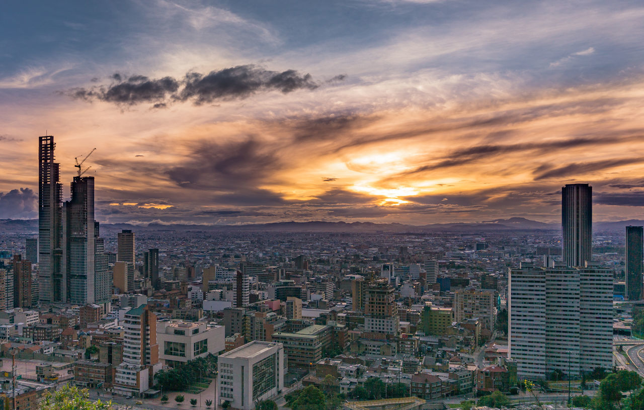 skyscraper, cityscape, city, architecture, sunset, building exterior, built structure, modern, cloud - sky, sky, tall - high, urban skyline, travel destinations, tower, skyline, development, no people, outdoors, downtown district, downtown, growth, tall, nature, day