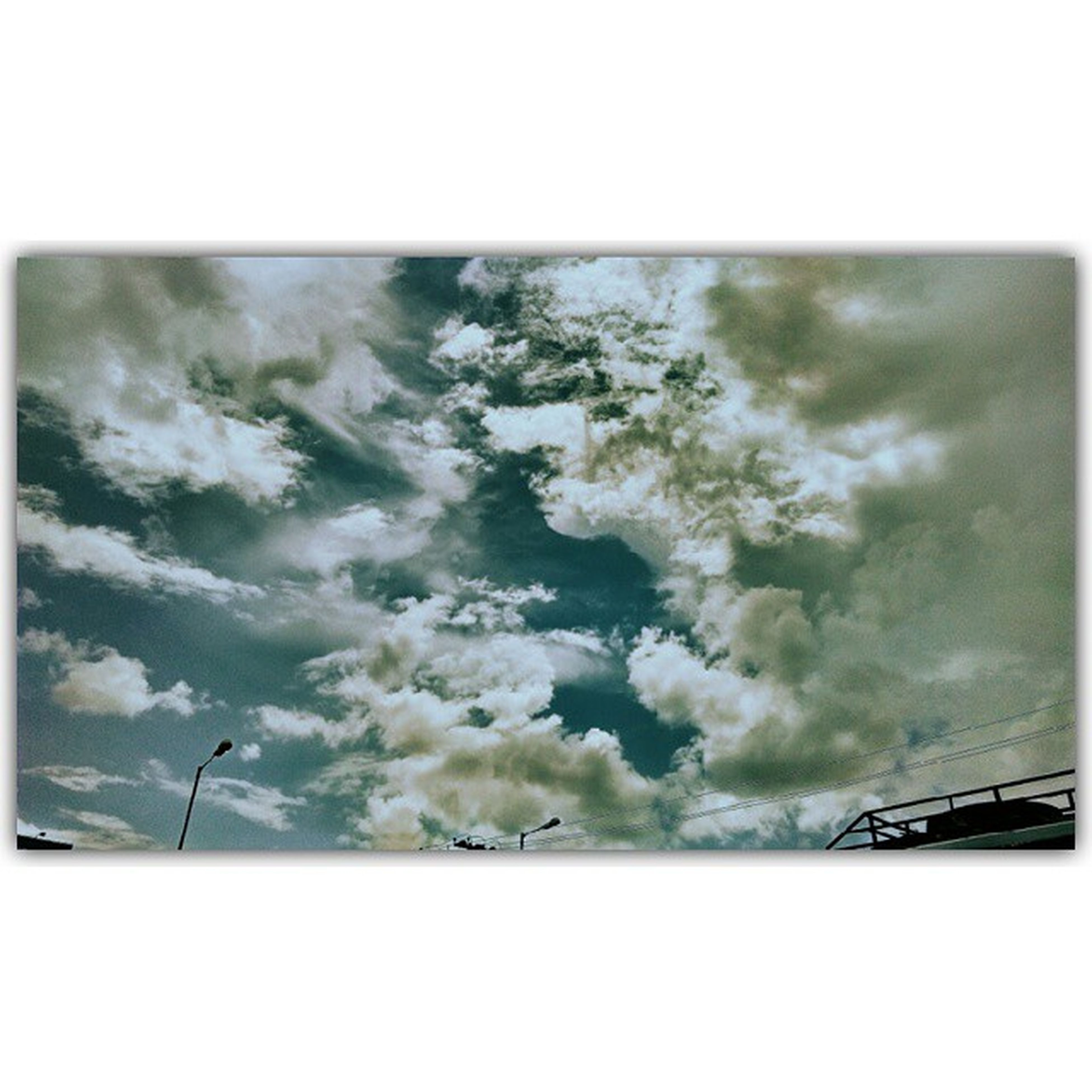 transfer print, auto post production filter, sky, transportation, cloud - sky, cloudy, mode of transport, low angle view, weather, overcast, railing, cloud, nature, outdoors, day, no people, connection, land vehicle, car, beauty in nature