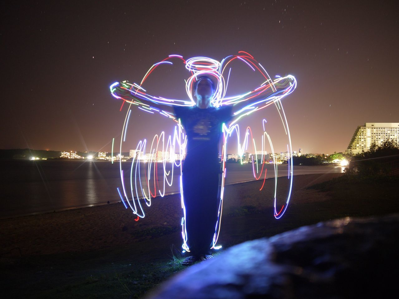 night, illuminated, long exposure, light painting, outdoors, one person, water, real people, motion, full length, sea, standing, blue, sky, wire wool, nature, people