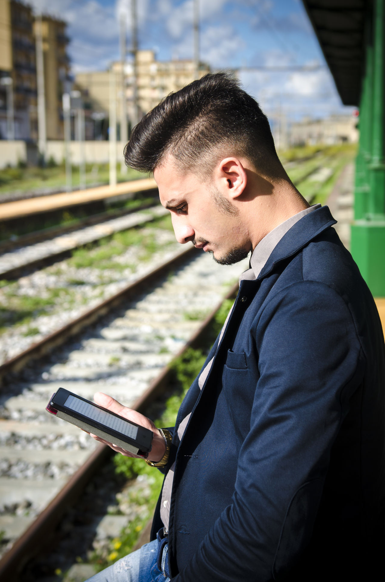 man reading a tablet or ebook in a train station while is waiting for public transport Beard City Ebook Human Body Part Men One Man Only One Person Only Men Outdoors Portable Information Device Portrait Reader Tablet Train Train Station Travel Trip Wireless Technology Young Adult