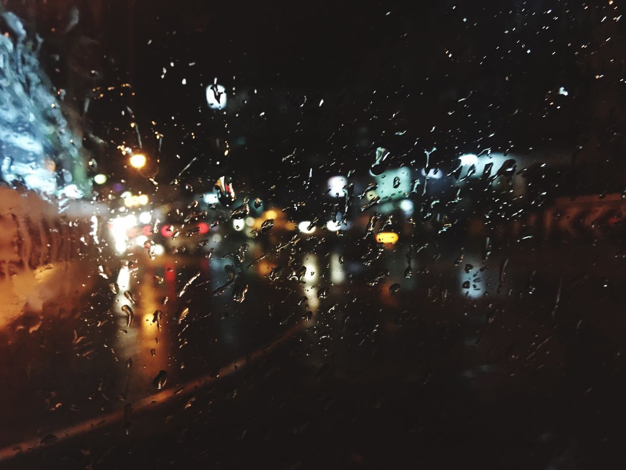 illuminated, window, wet, glass - material, night, weather, car, no people, raindrop, drop, car interior, windshield, transportation, land vehicle, indoors, water, close-up, sky
