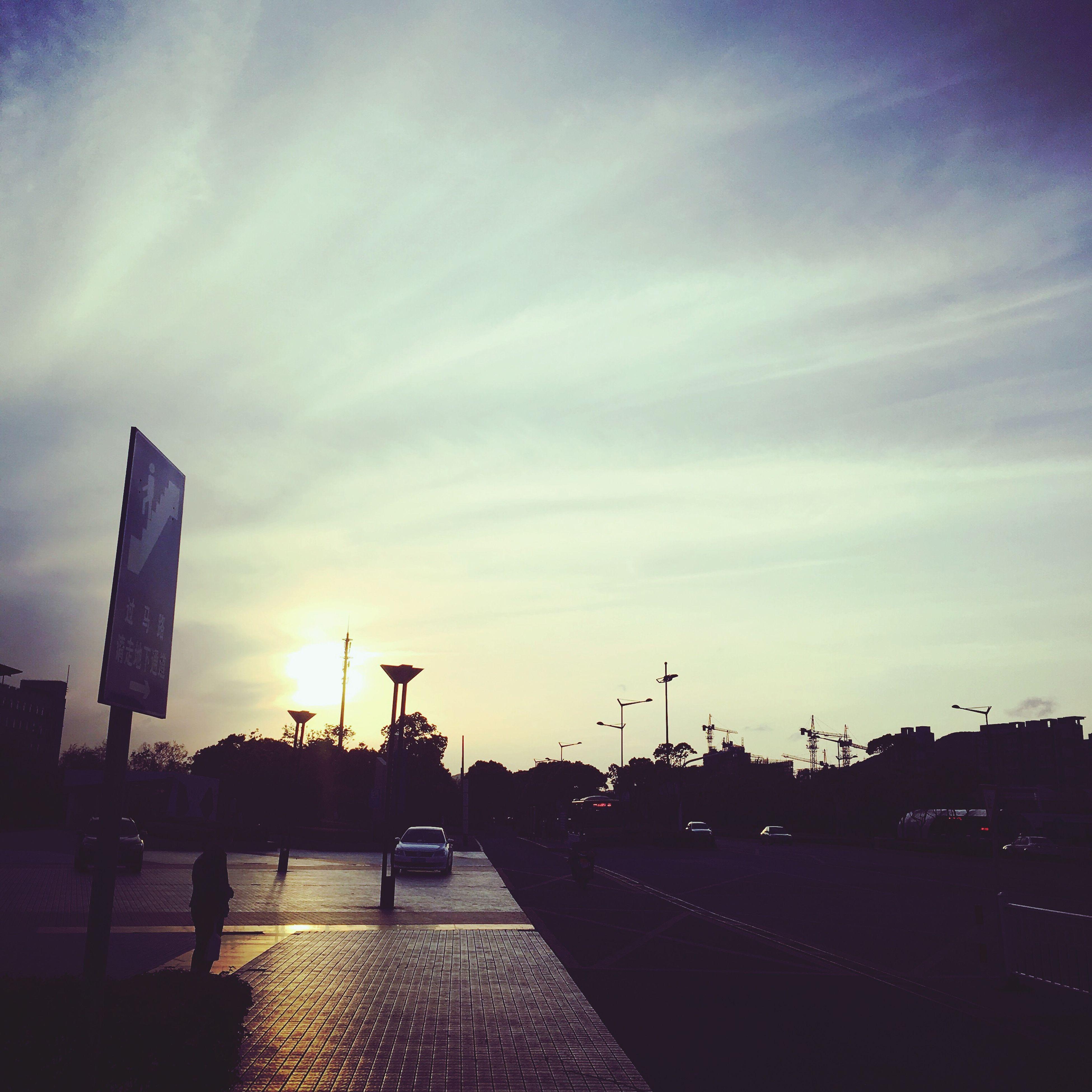 sky, sunset, built structure, architecture, building exterior, silhouette, cloud - sky, city, cloud, sunlight, transportation, road, cloudy, outdoors, dusk, street, no people, orange color, the way forward, nature