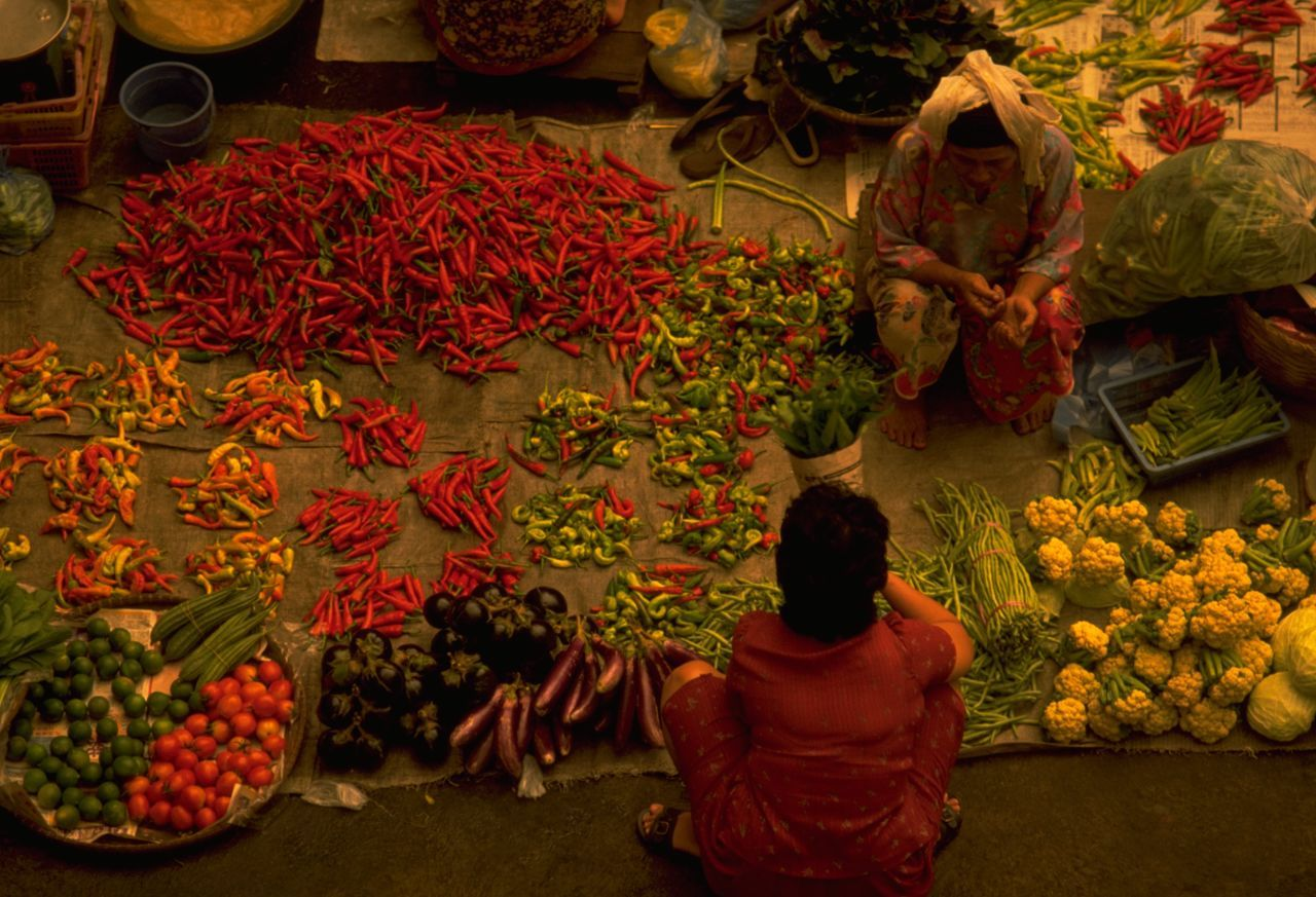 Vegetable Market in Kota Bharu, Malaysia. Vegetable markets are a great place for colourful pictures of local life. What could be more traditional that the morning ritual of shopping for fresh produce to put on the table. Here at this indoor market in Malaysia, local farmers spread out their produce on the floor. Potential customers then crouch to select their ingredients and discuss the price; oblivious of the travel photographer behind them. http://pics.travelnotes.org/ Adults Only ASIA Authentic Crouching Daily Life Food Fresh Produce Kota Bharu Local Malaysia Market Market Vendor Markets Michel Guntern On The Floor Real People Red Peppers Travel Travel Photography Travel Photos Travel Pics Two People Snap A Stranger Vegetable Market Beautifully Organized