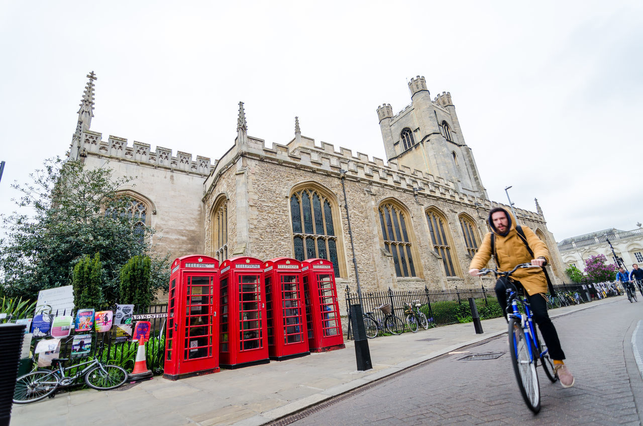 Adult Architecture Bicycle Building Exterior Built Structure Cambridge University Cambridgeshire City Day Full Length Leisure Activity Lifestyles Men One Person Outdoors People Real People Sky Telephone Booth Tourism Travel Destinations United Kingdom Vacations Women Young Adult