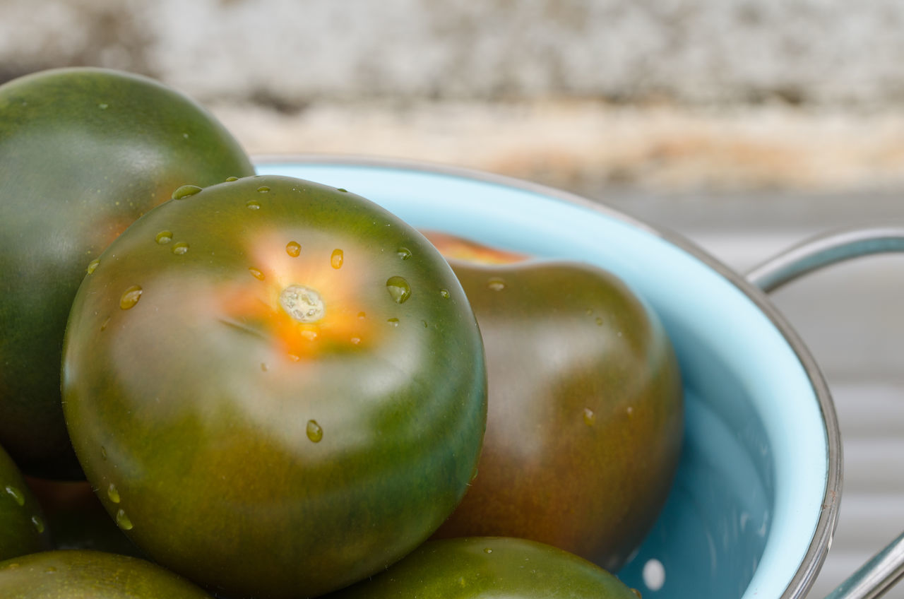 Close-Up Of Unripe Tomatoes In Colander On Table