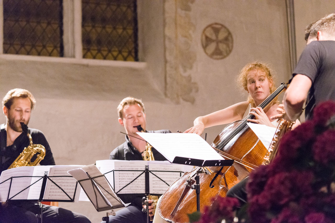 music, musician, playing, musical instrument, performance, arts culture and entertainment, sheet music, real people, practicing, music stand, classical music, cello, violin, indoors, young women, young adult, performing arts event, skill, sitting, togetherness, classical concert, day, performance group, people