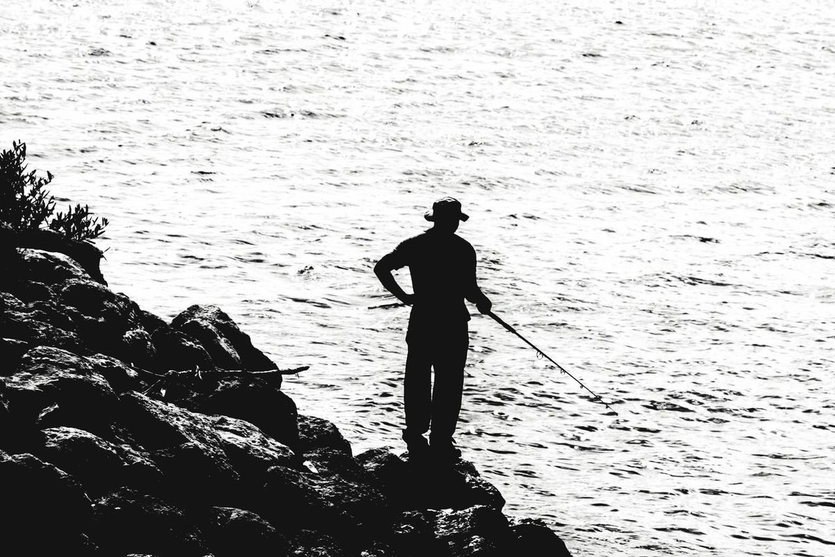 Fisherfolk. Real People One Person Standing Water Leisure Activity Sea Outdoors Men Full Length Lifestyles Day Nature EyeEm Nature Lover 876EyeEm Tranquil Scene EyeEmNewHere Silhouette Water_collection