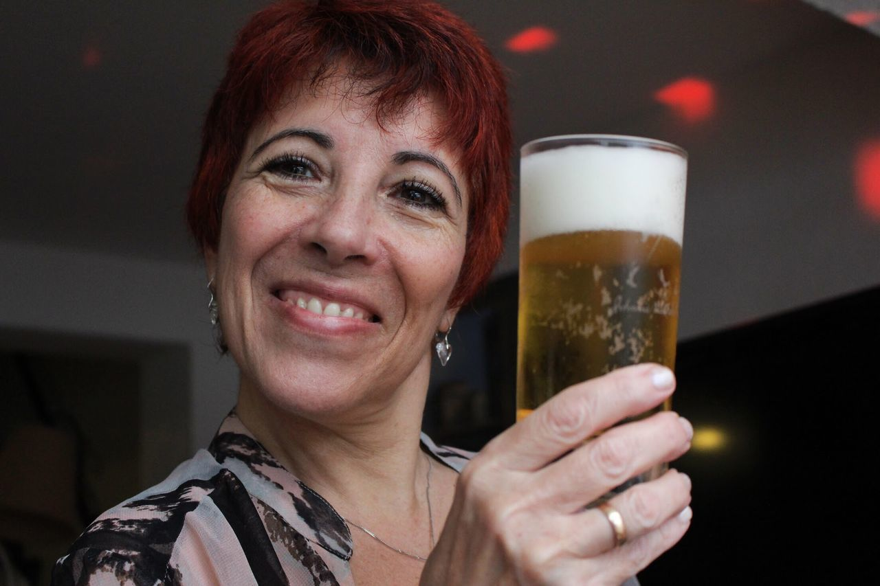 beer glass, beer - alcohol, smiling, alcohol, drink, happiness, real people, one person, refreshment, cheerful, focus on foreground, beer, food and drink, leisure activity, looking at camera, close-up, portrait, headshot, frothy drink, outdoors, night, freshness, adult, people