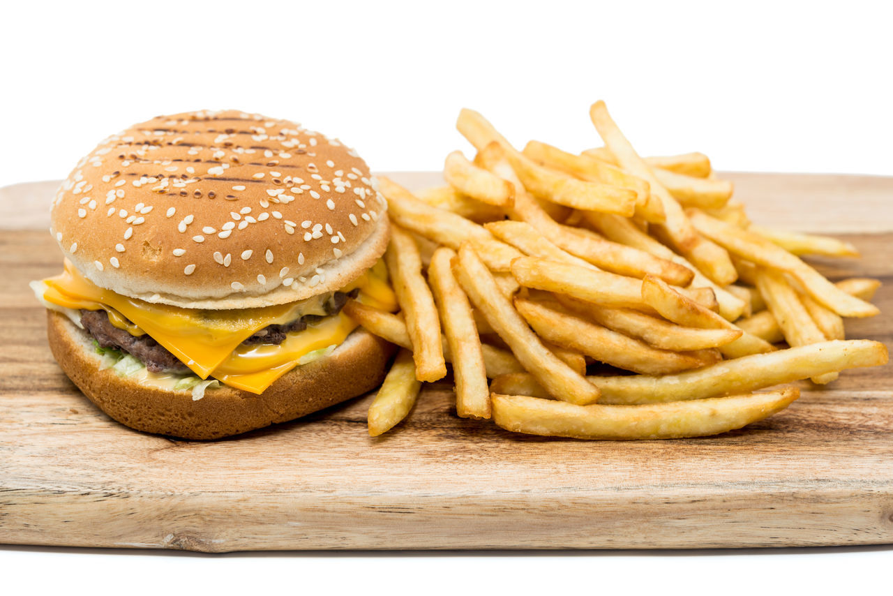 Burger And French Fries On Cutting Board Against White Background
