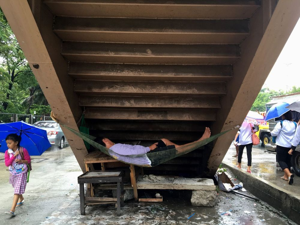 A man sleeps on a hammock under a footbridge in Taguig, Metro Manila. Hammock Hammock Time Hammocktime Sleeping Sleep Time Under The Bridge Taguig Philippines Metro Manila