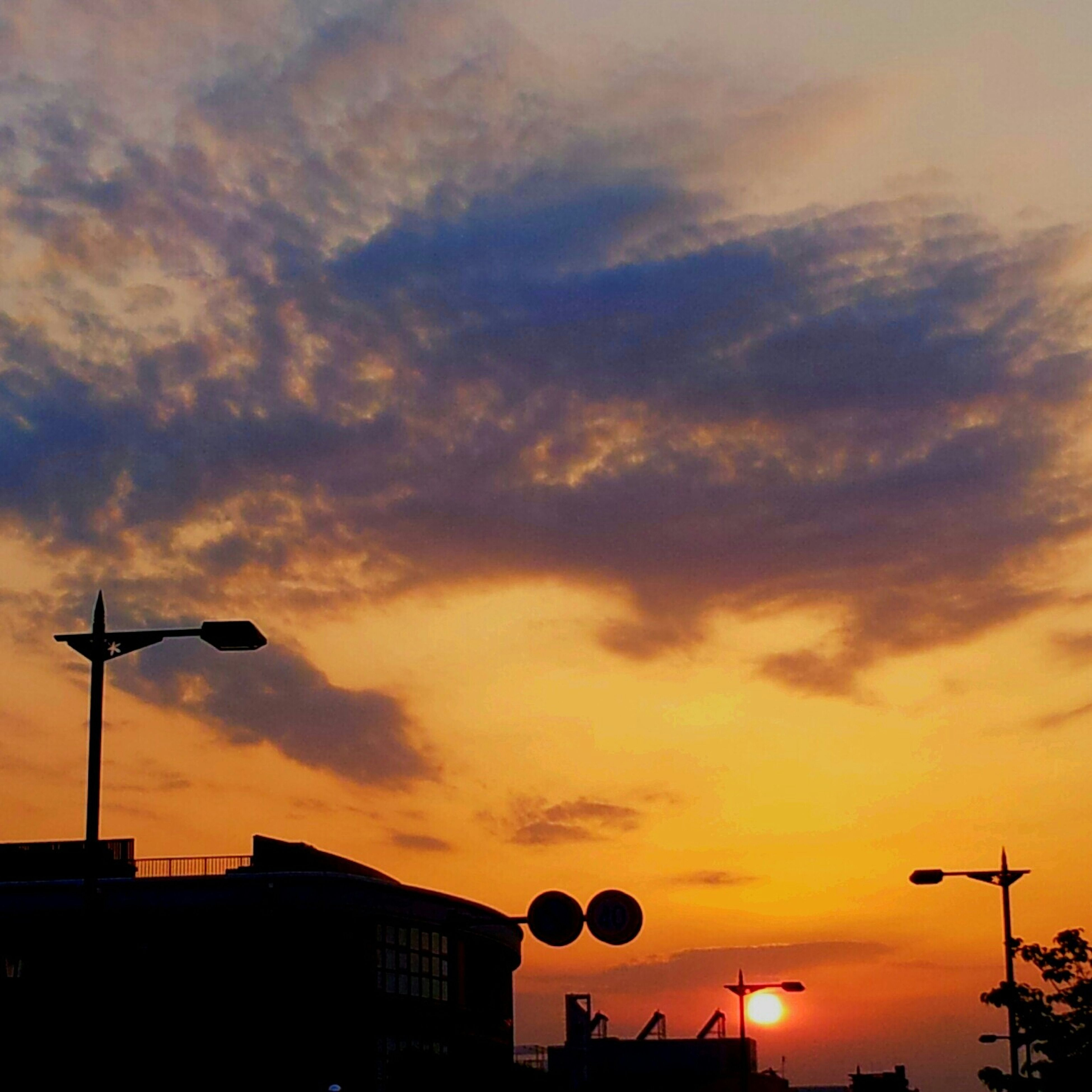 sunset, silhouette, sky, orange color, low angle view, cloud - sky, street light, building exterior, built structure, architecture, communication, dramatic sky, cloudy, cloud, nature, high section, beauty in nature, outdoors, lighting equipment, scenics