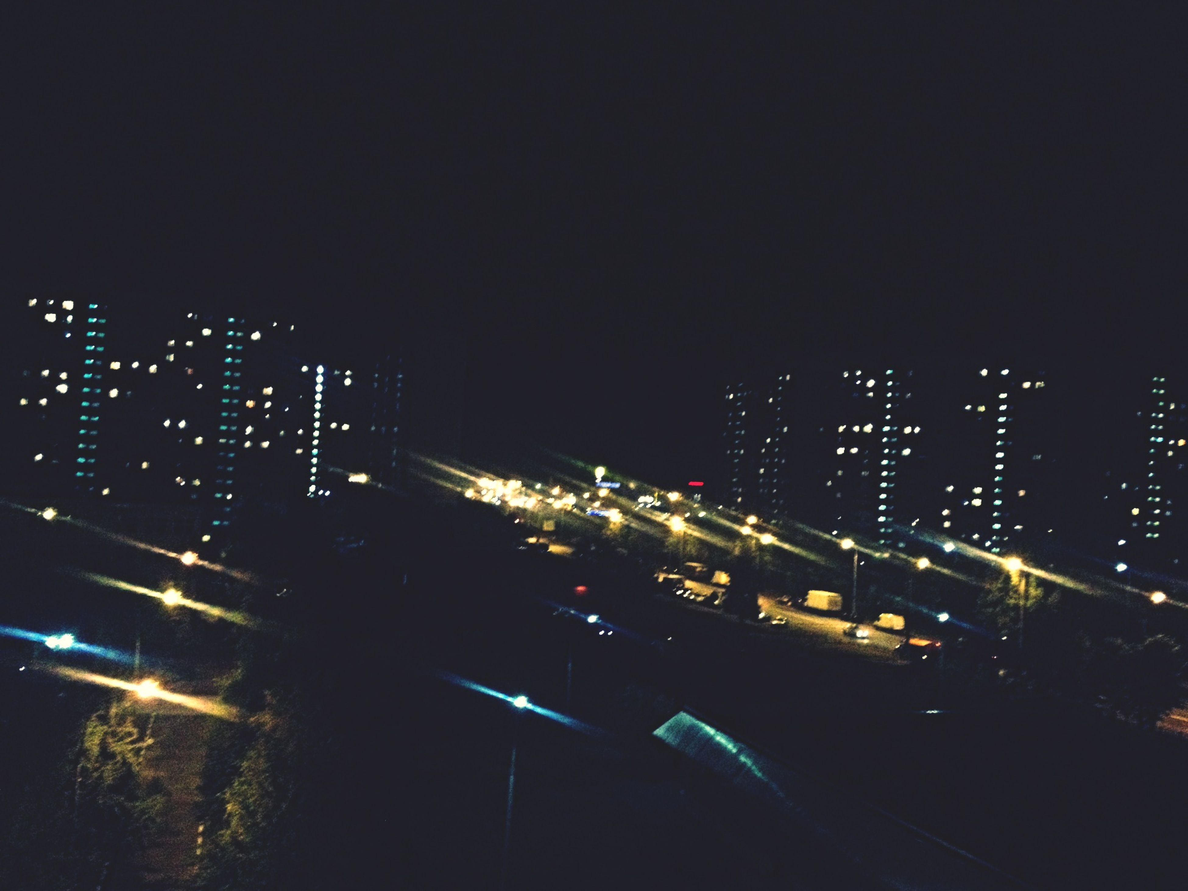 illuminated, night, building exterior, city, architecture, built structure, skyscraper, tall - high, modern, office building, city life, tower, high angle view, cityscape, development, transportation, building, outdoors, street, light - natural phenomenon