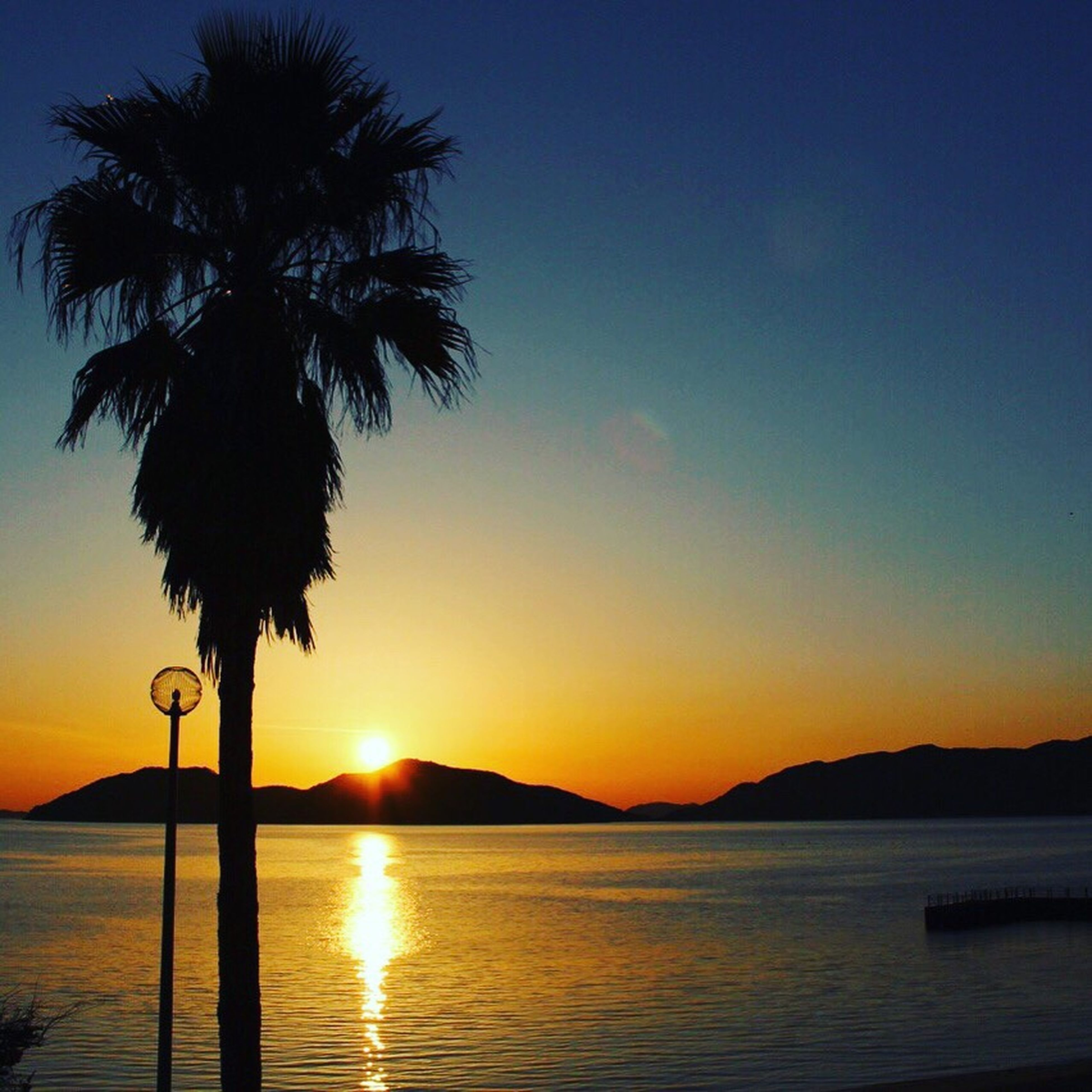 sunset, water, tranquil scene, scenics, silhouette, sea, tranquility, beauty in nature, sun, palm tree, orange color, idyllic, nature, mountain, sky, reflection, horizon over water, tree, clear sky, majestic